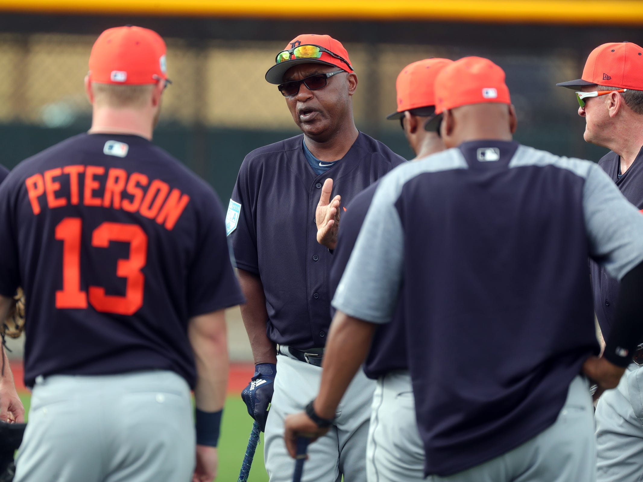 Tigers coach Dave Clark talks to outfielders during spring training Wednesday, Feb. 20, 2019, at Joker Marchant Stadium in Lakeland, Fla.