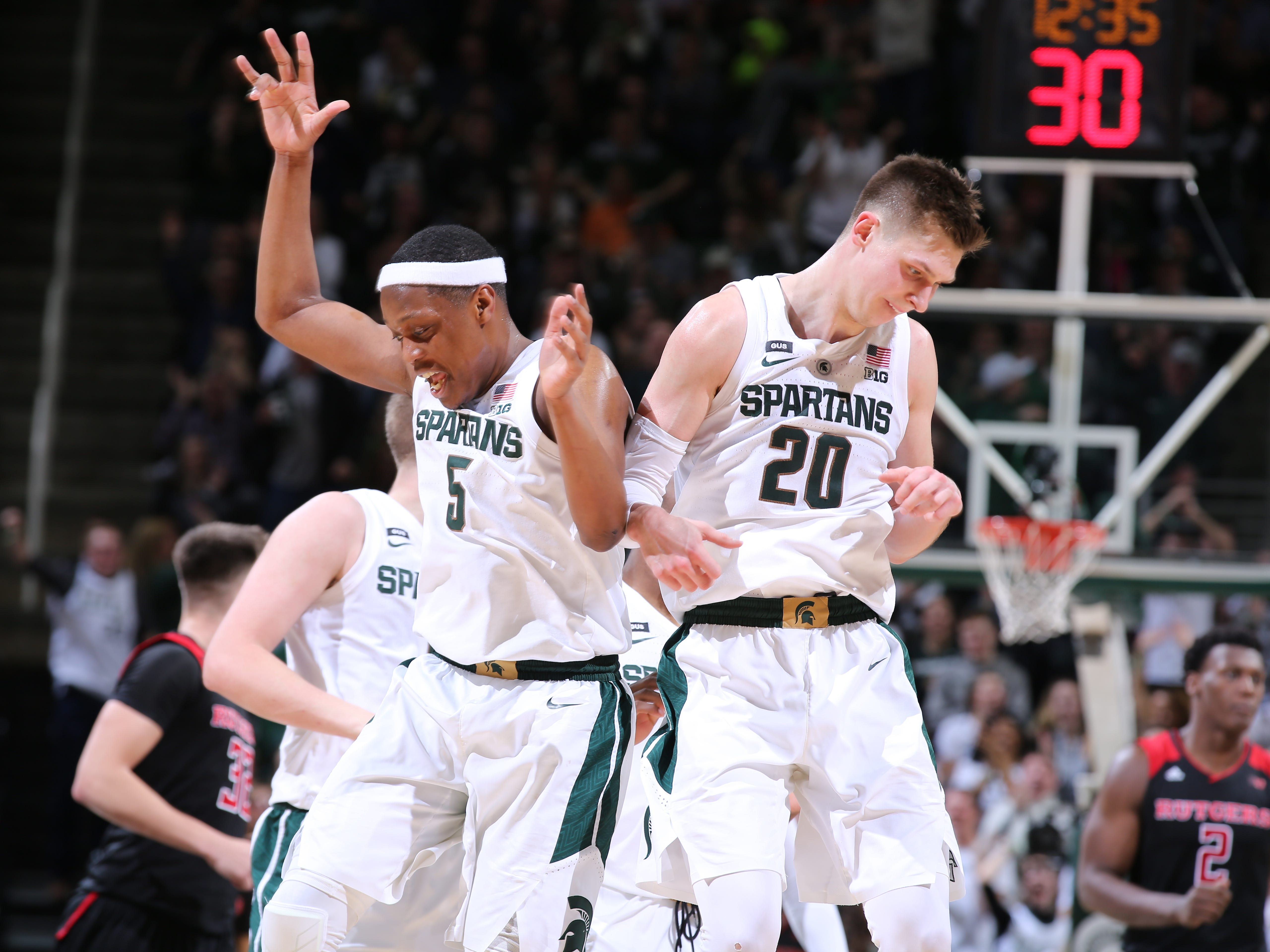 Matt McQuaid #20 of the Michigan State Spartans celebrates his three-point basket in the second half with teammate Cassius Winston #5 of the Michigan State Spartans against the Rutgers Scarlet Knights at Breslin Center on February 20, 2019 in East Lansing, Michigan.