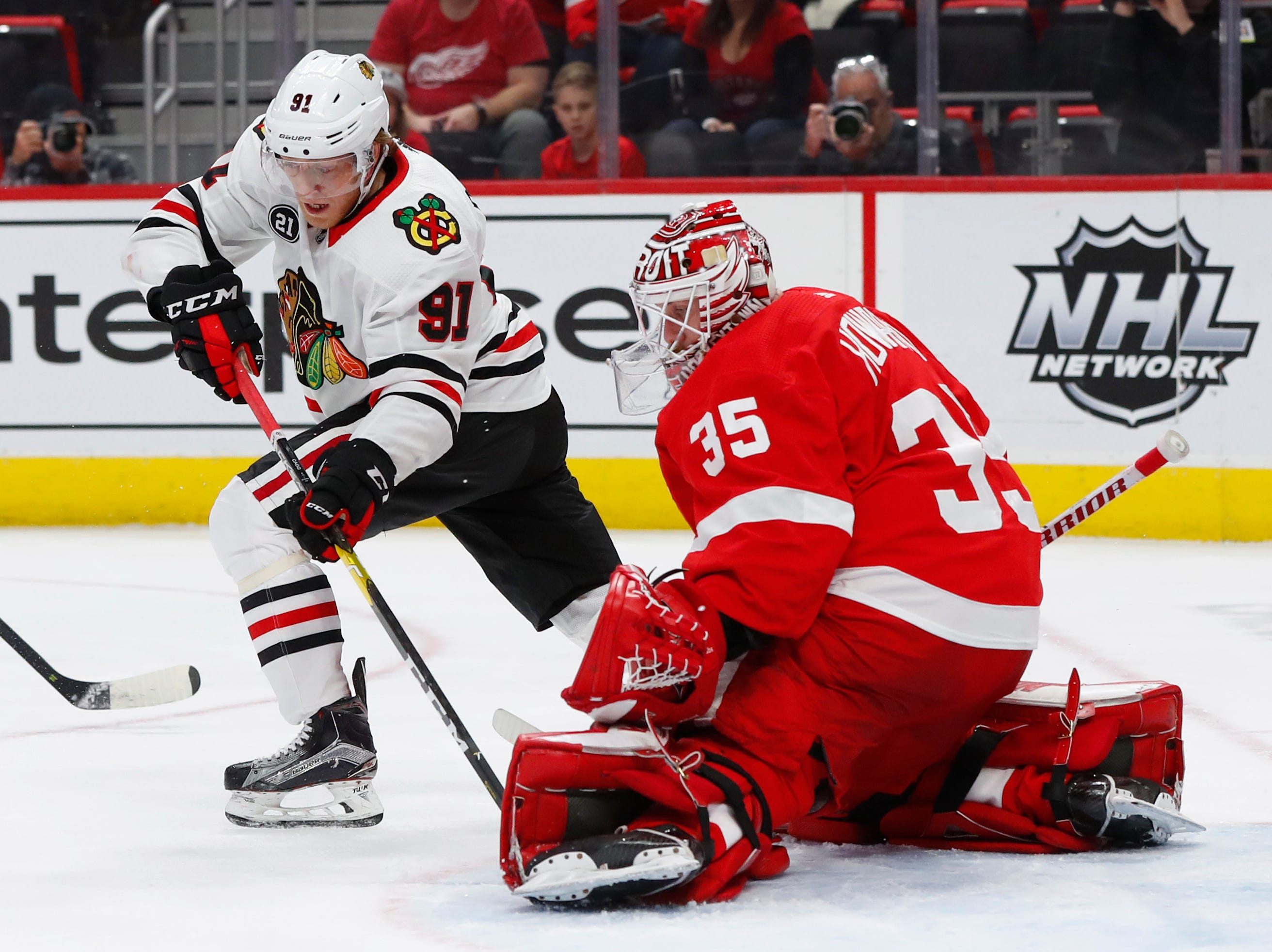 Detroit Red Wings goaltender Jimmy Howard, right, stops a Chicago Blackhawks center Drake Caggiula, left, shot in the first period of an NHL hockey game Wednesday, Feb. 20, 2019, in Detroit.