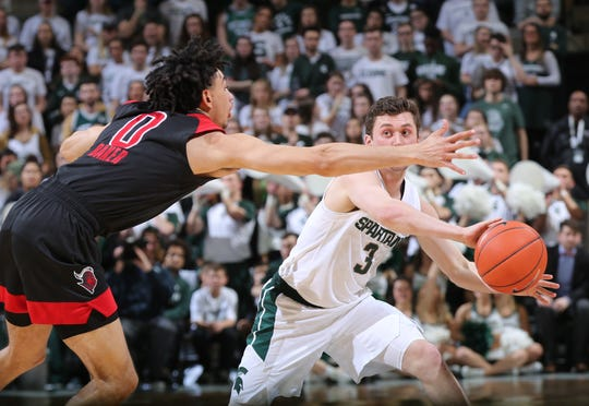 Foster Loyer #3 of the Michigan State Spartans looks to pass the ball while defended by Geo Baker  #0 of the Rutgers Scarlet Knights in the first half  at Breslin Center on February 20, 2019 in East Lansing, Michigan.