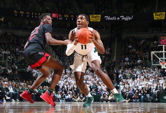 AAron Henry #11 of the Michigan State Spartans drives to the basket while defended by Montez Mathis #23 of the Rutgers Scarlet Knight in the first half at Breslin Center on February 20, 2019 in East Lansing, Michigan.