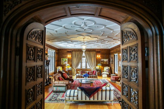 Two massive oak doors carved with various heads and designs lead into the lavish living room in this 1927 Windmill Pointe mansion. Just before these doors, the foyer holds both his and her powder rooms for guests. The 1927 Tudor, historically referred to as Bellmor, was photographed for House Envy on Wednesday, Feb. 20, 2019.