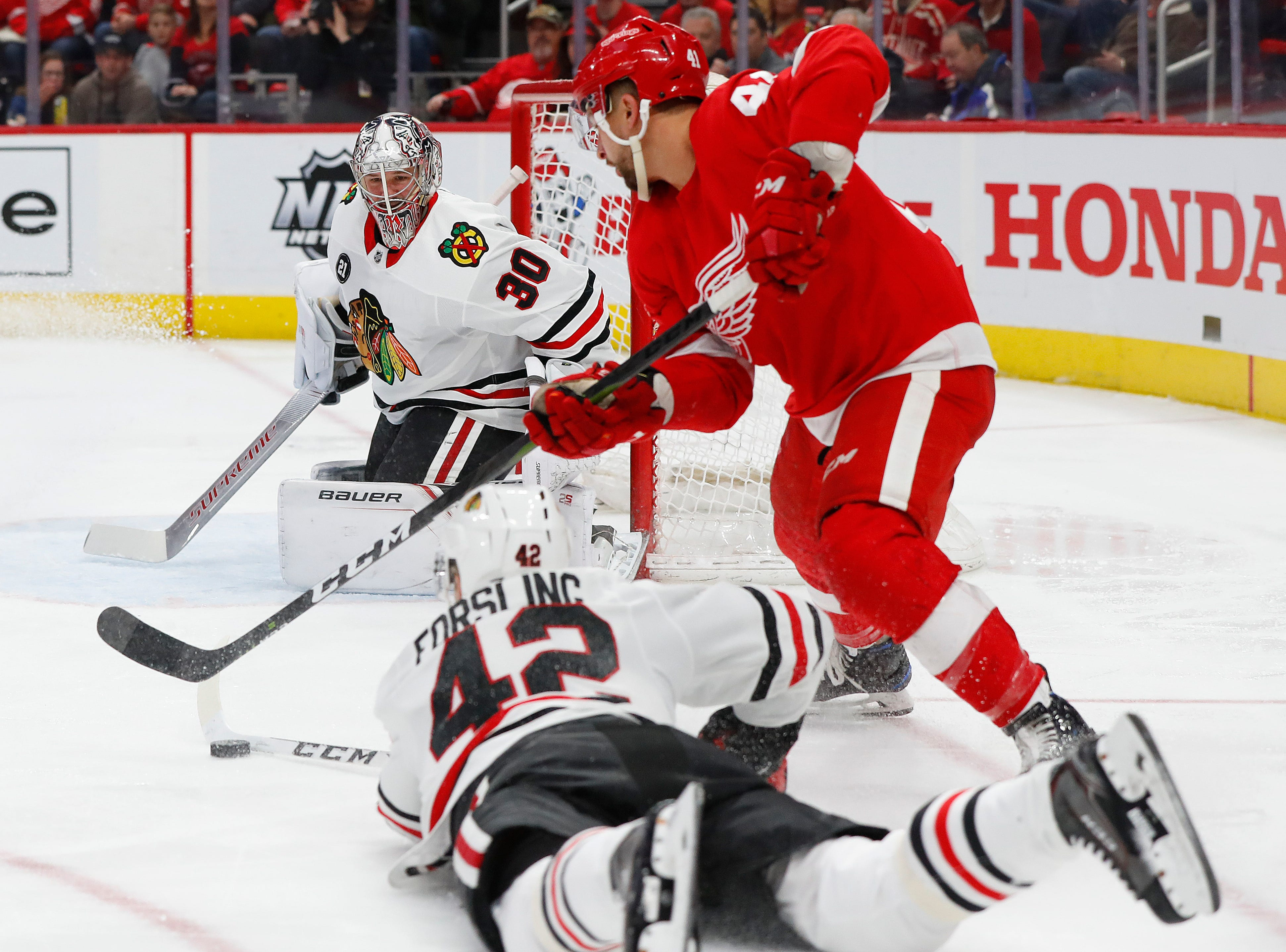 Chicago Blackhawks defenseman Gustav Forsling (42) takes the puck from Detroit Red Wings center Luke Glendening (41) in front of Cam Ward (30) in the second period of an NHL hockey game Wednesday, Feb. 20, 2019, in Detroit.