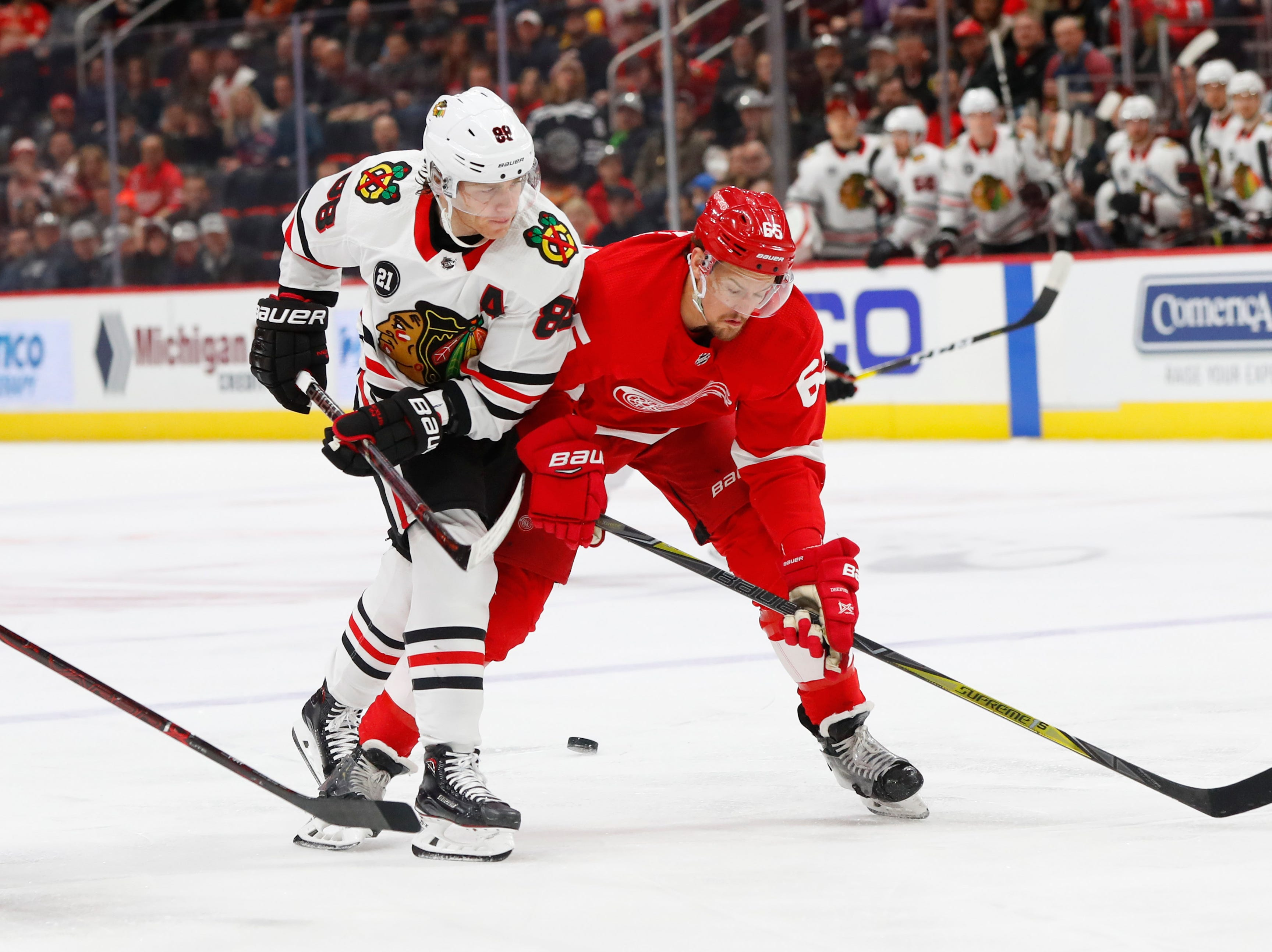 Detroit Red Wings defenseman Danny DeKeyser, right, knocks Chicago Blackhawks right wing Patrick Kane, left, off the puck in the first period of an NHL hockey game Wednesday, Feb. 20, 2019, in Detroit.