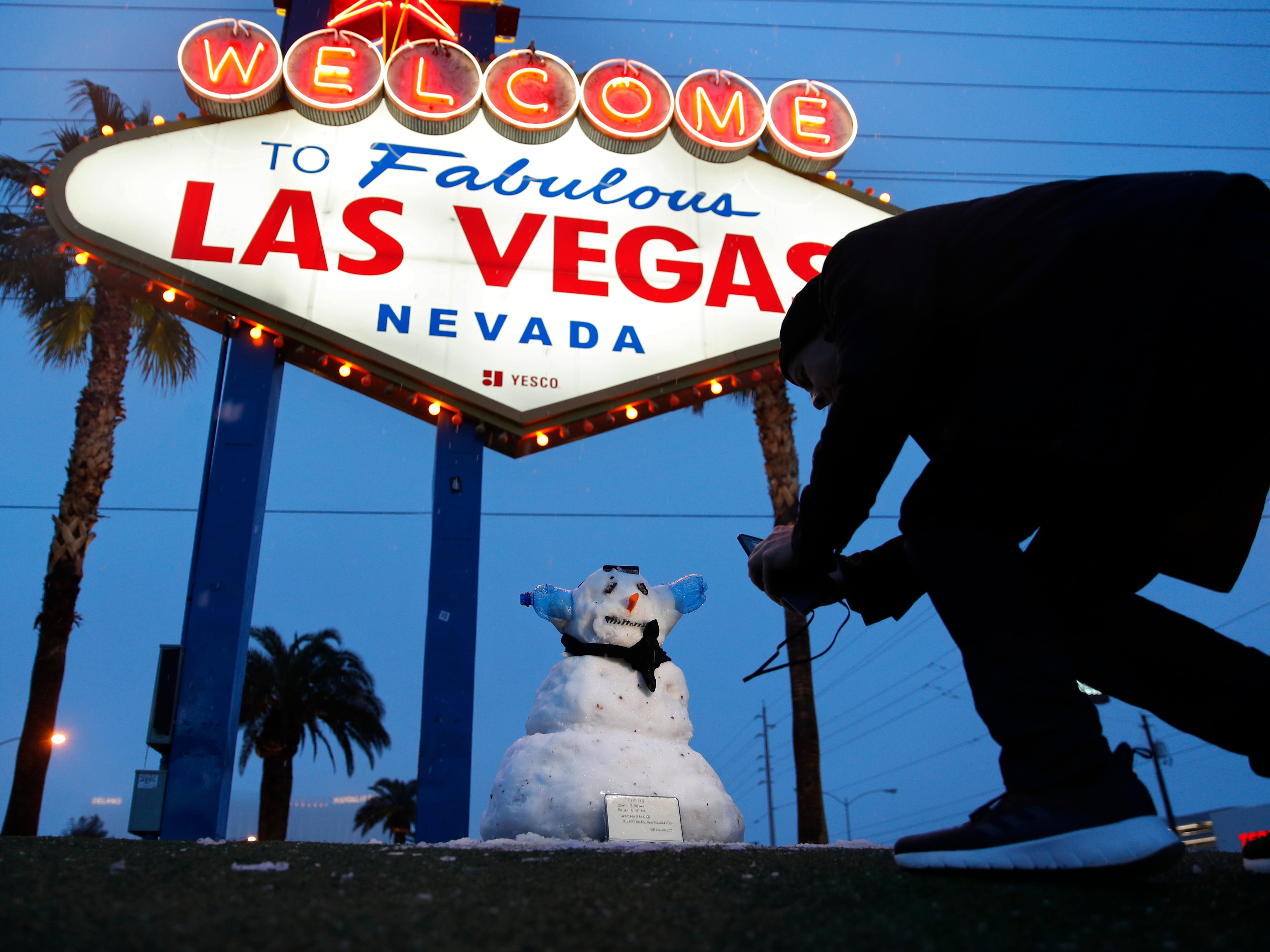 """A man takes a picture of a small snowman at the """"Welcome to Fabulous Las Vegas"""" sign along the Las Vegas Strip, Thursday, Feb. 21, 2019, in Las Vegas. Las Vegas is getting a rare taste of real winter weather, with significant snowfall across the metro area in the first event of its kind since record-keeping started in 1937."""