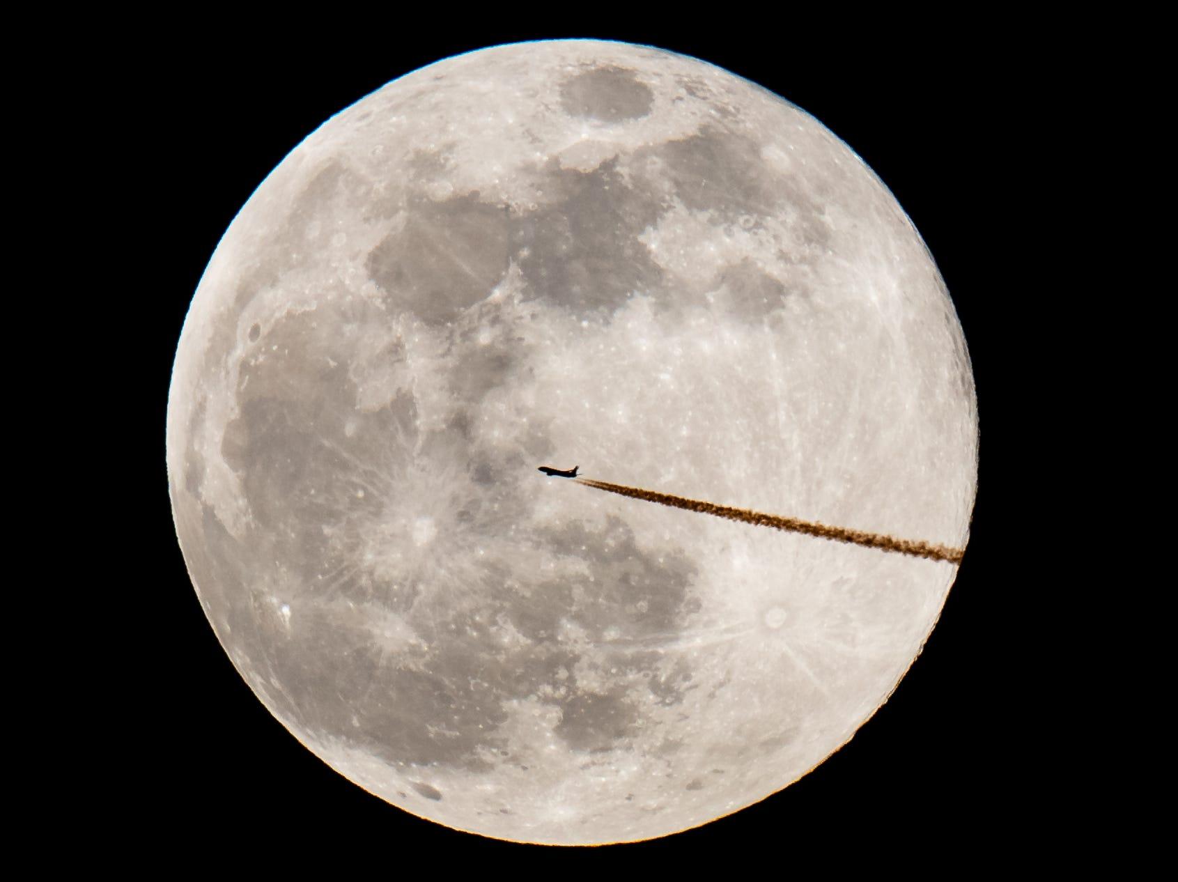 A plane flies past a full moon in Nuremberg on Feb. 19, 2019.
