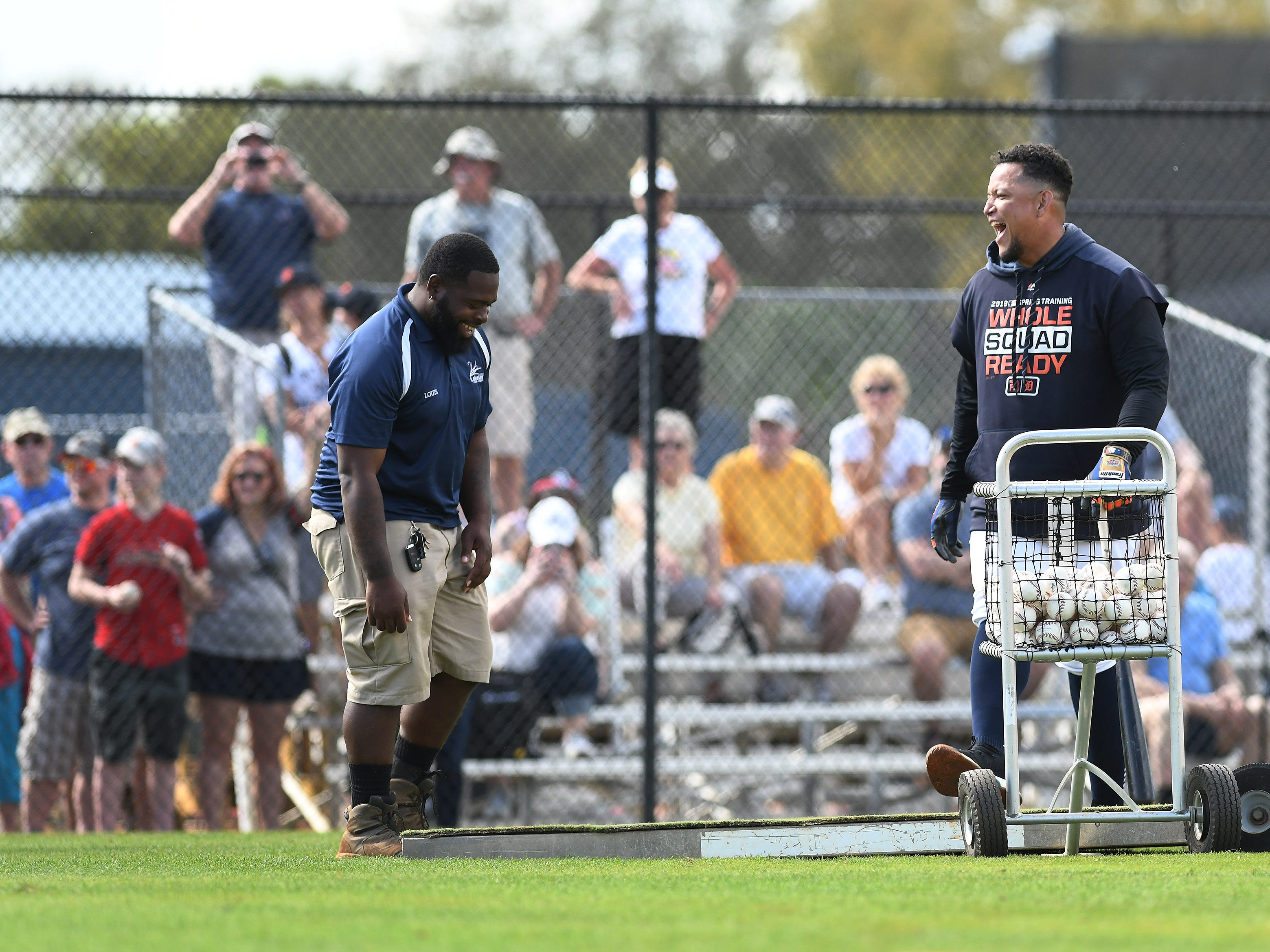 Ground crew member Louis Matos, left, says something to make Tigers slugger Miguel Cabrera laugh while the field is changed over for the next round of batting practice.