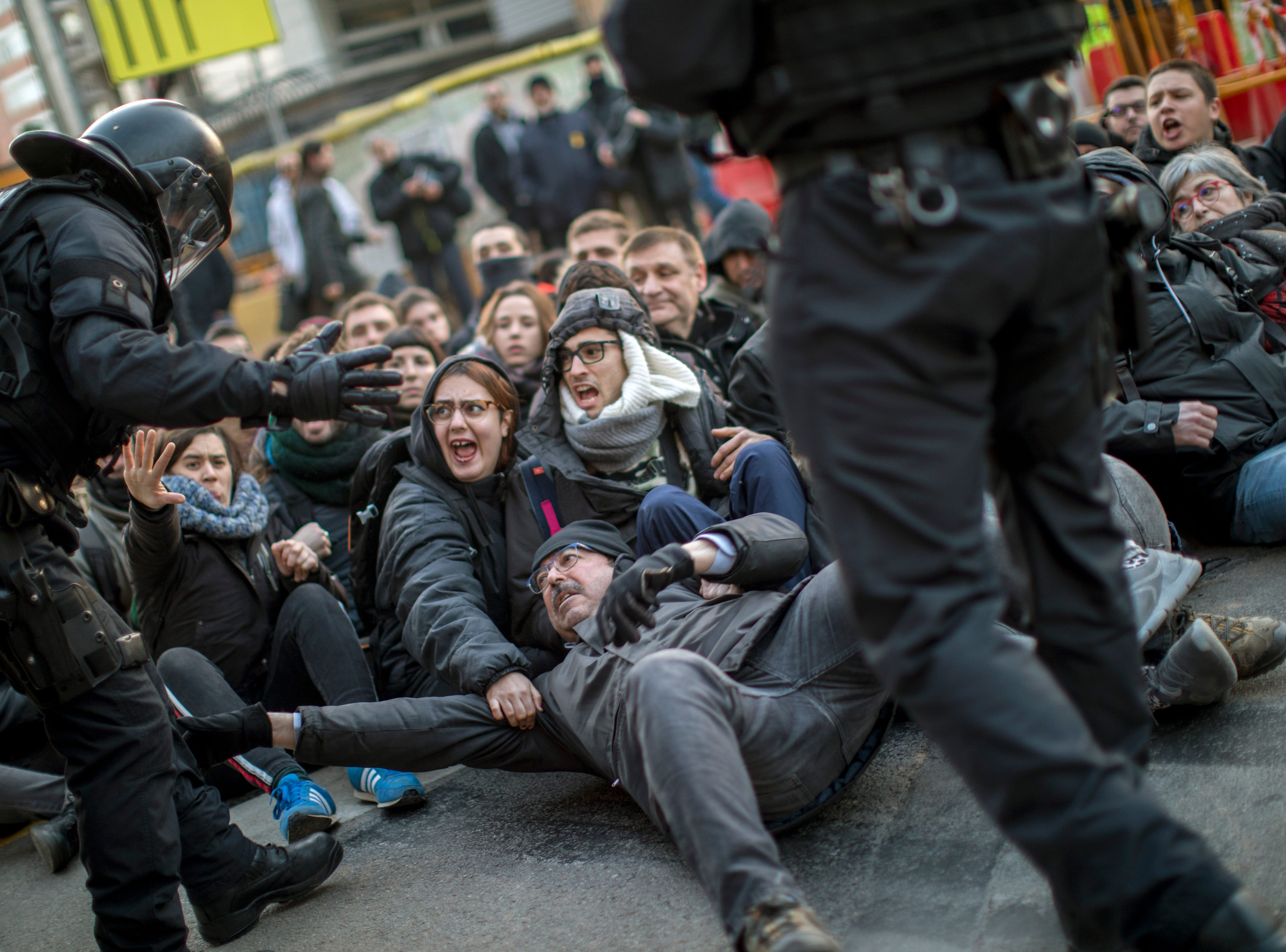 Police officers remove demonstrators blocking a road leading to Barcelona city during a general strike in Catalonia, Spain, Thursday, Feb. 21, 2019. Strikers advocating for Catalonia's secession from Spain are blocking major highways, train lines and roads across the northeastern region.