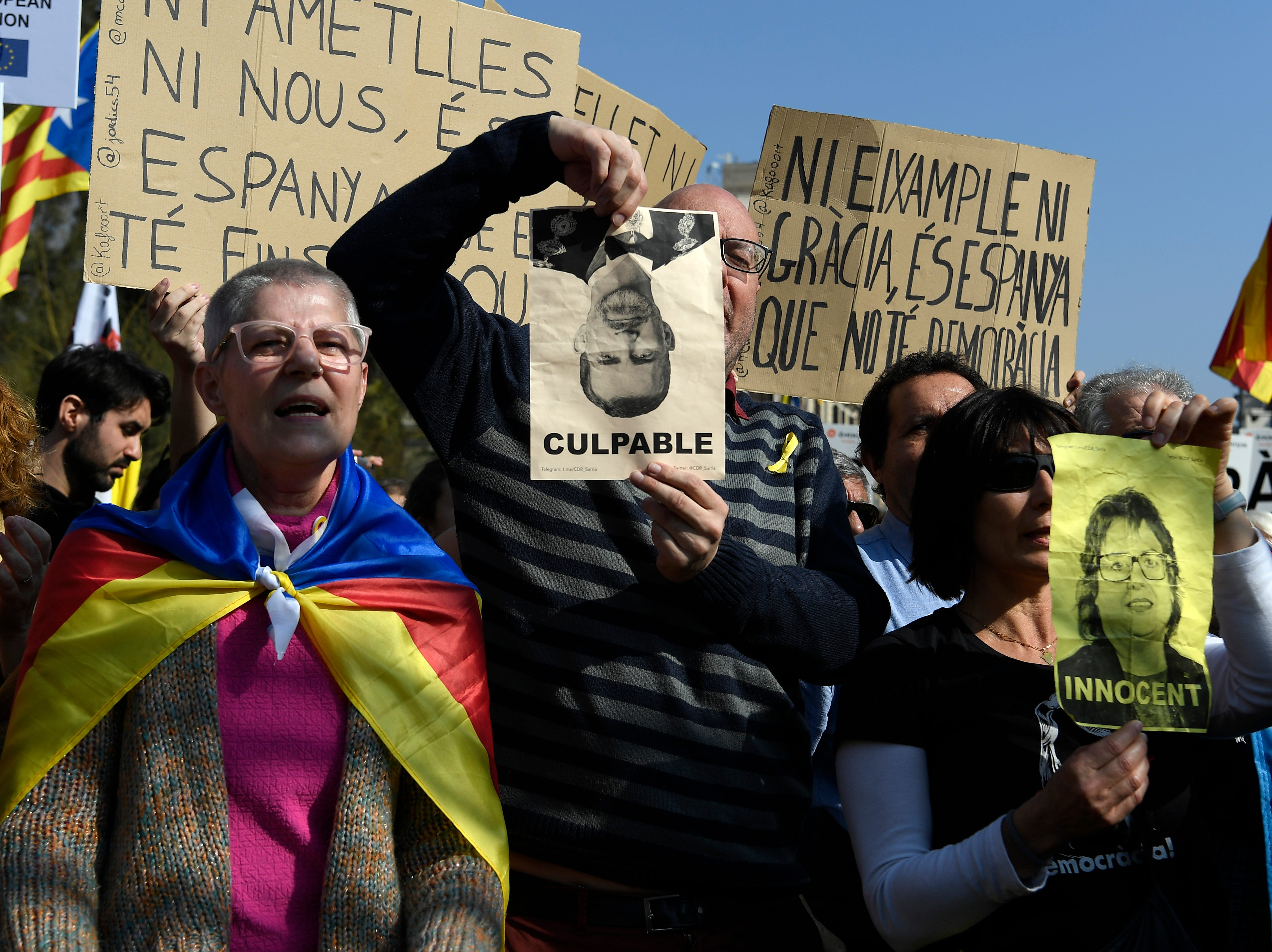 """A man holds a photograph of king Felipe VI with the legend """"culpable"""" during a protest in Barcelona against the trial of former Catalan separatist leaders in Madrid, during a strike day on Feb. 21, 2019."""
