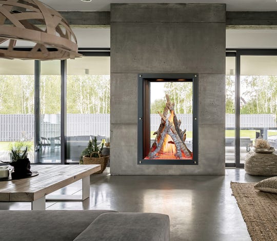 """A dramatic log set arranged in a vertical fashion serves as a transition to outdoors when placed into a large see-through fireplace wall unit. Manufactured by Travis Industries, Inc., this DaVinci Custom Fireplace features the """"Bon-Fyre"""" log set."""