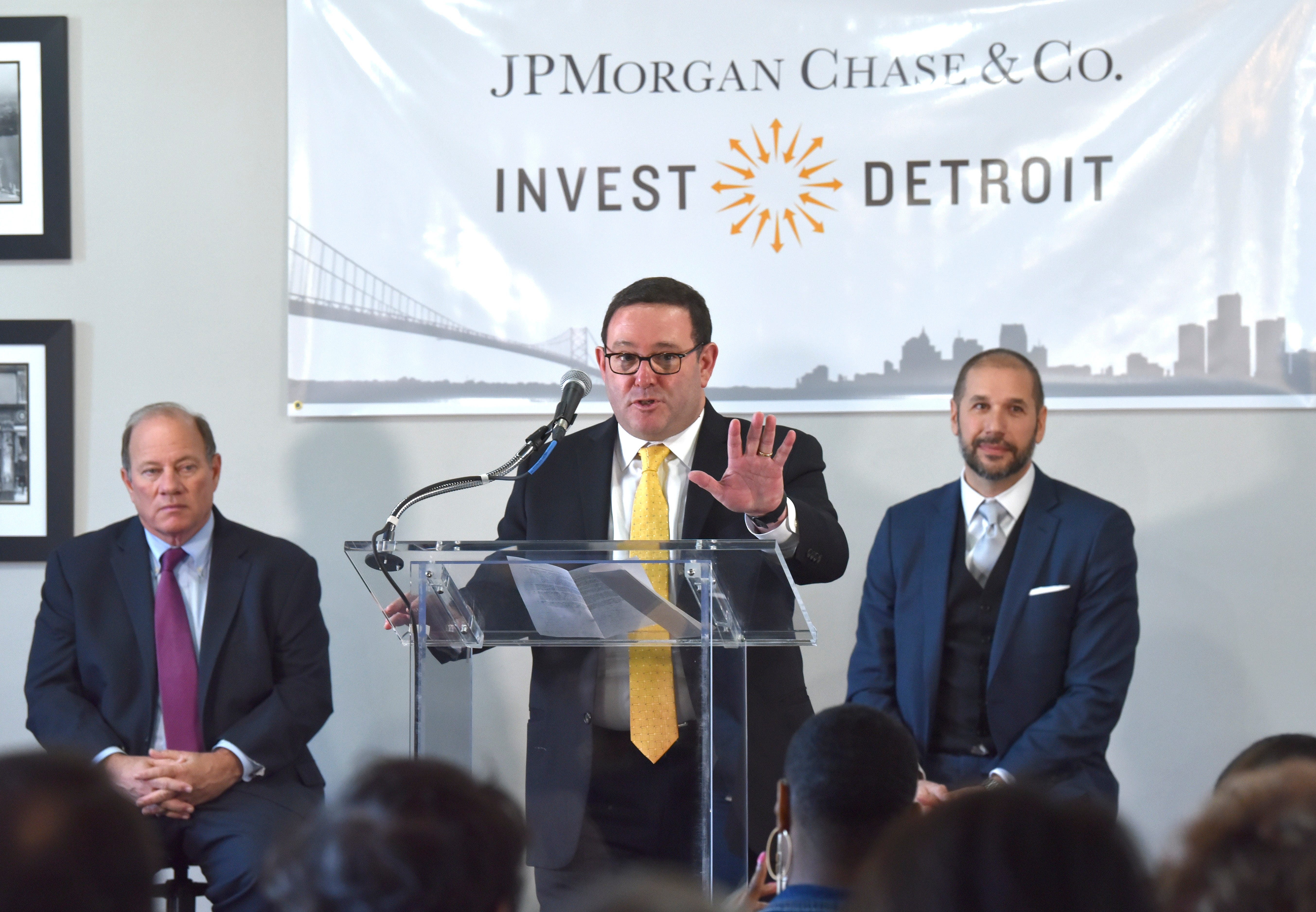 Peter Scher, center, head of corporate responsibility at JPMorgan Chase, announces a $15 investment in Detroit neighborhoods as Detroit Mayor Mike Duggan, left, and Invest Detroit CEO Dave Blaszkiewicz, right, listen.