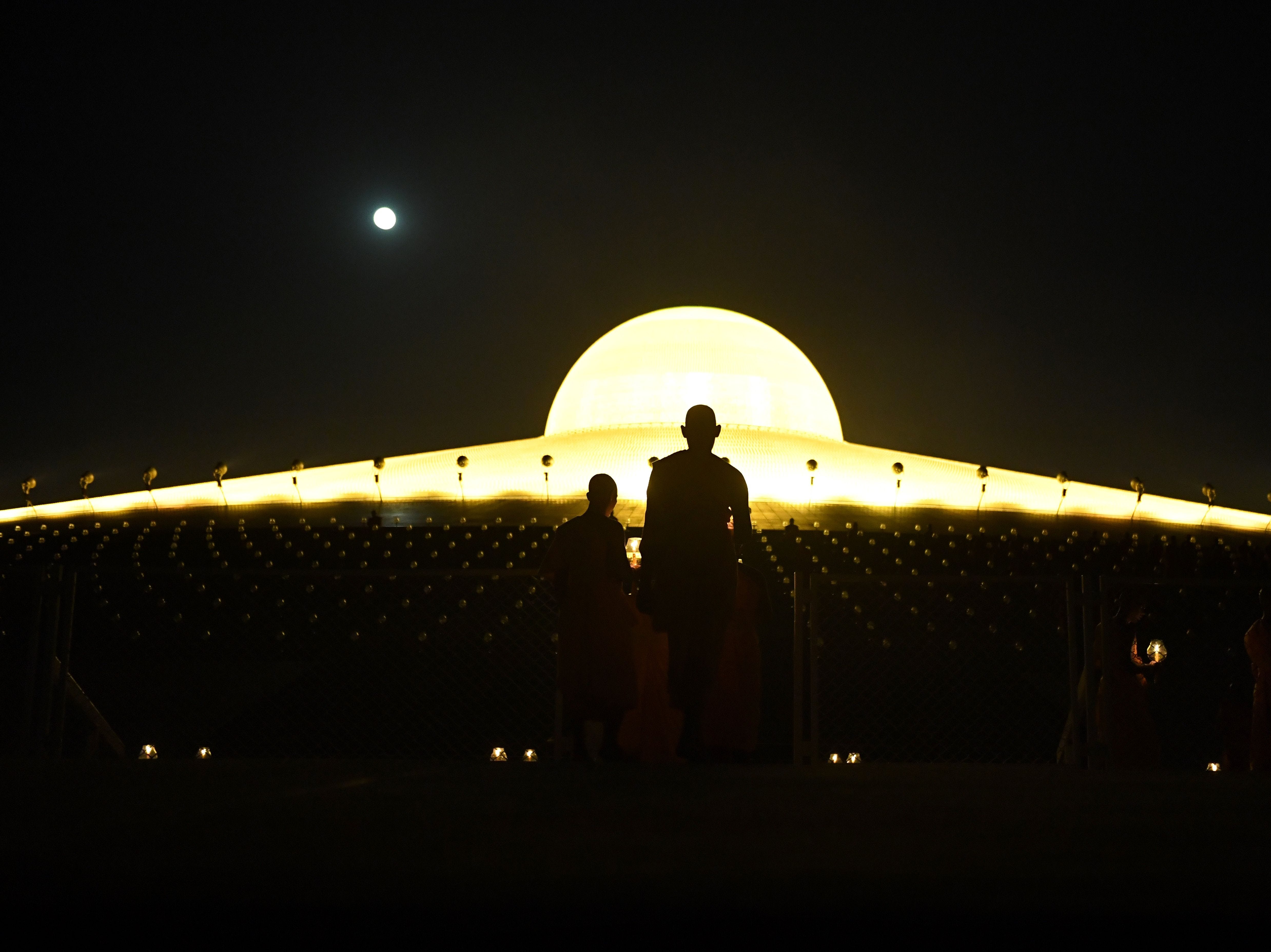 This photo taken on Feb. 19, 2019 shows Buddhist monks carrying lit candles while the full moon rises during prayers to mark Makha Bucha Day at the Wat Phra Dhammakaya temple, near Bangkok.