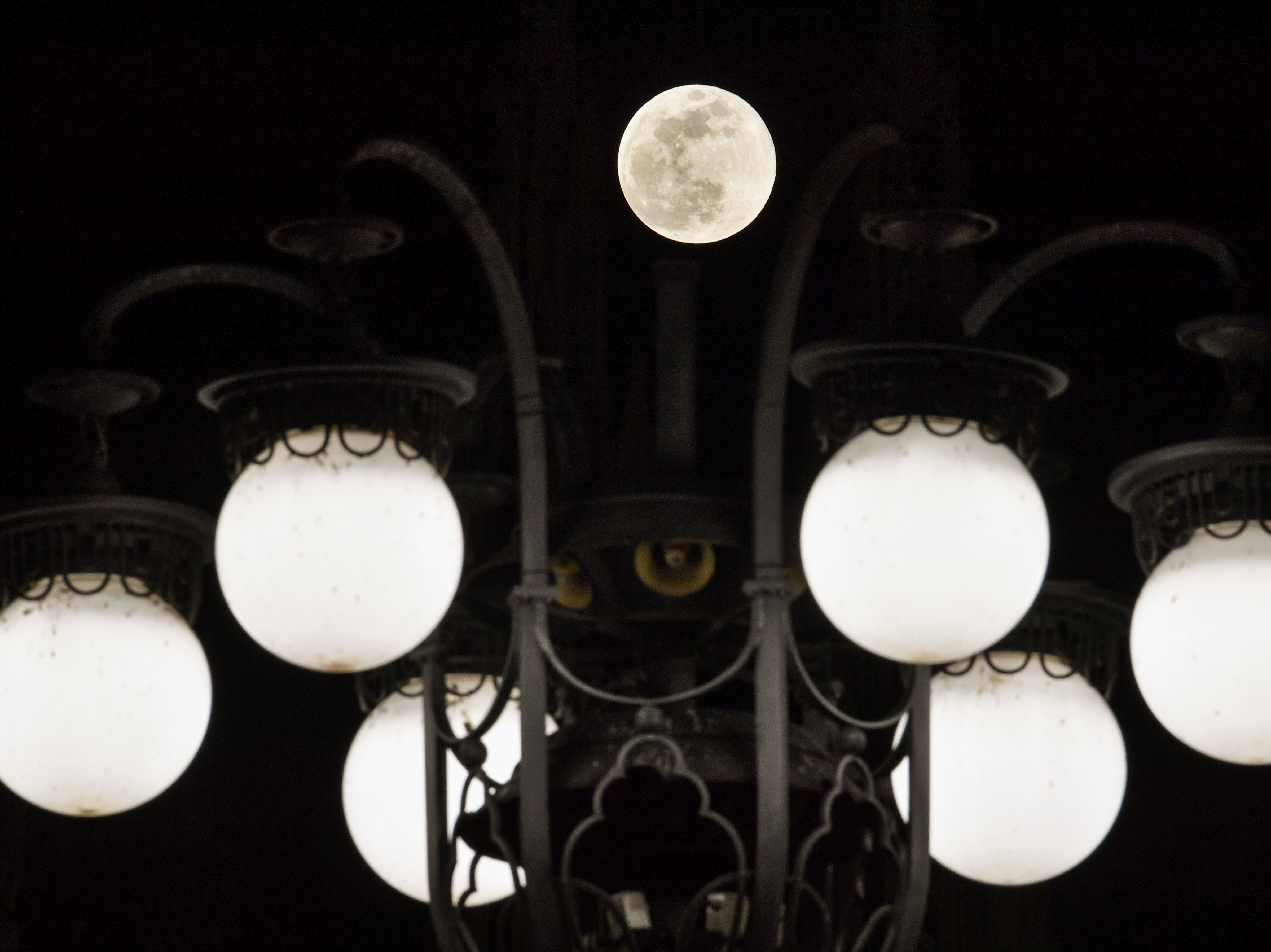 The Super Snow Moon is pictured against the street lights of Piazza del Duomo in downtown Milan on Feb. 19, 2019.