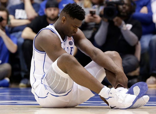 Duke's Zion Williamson sits on the floor following a knee injury during the first half.