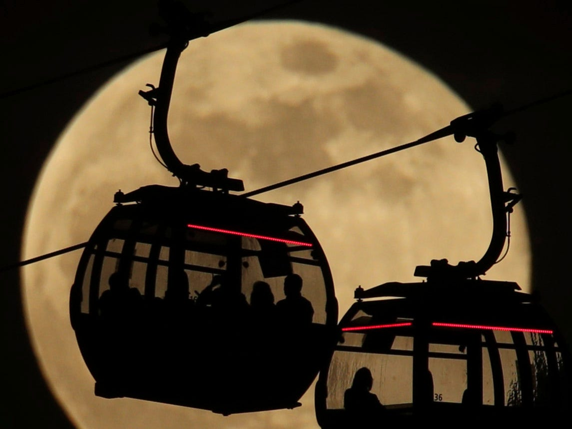 Emirates Air Line cable cars are silhouetted against the backdrop of the 'supermoon' in Greenwich, London, Tuesday, Feb. 19, 2019. Tuesday's full moon, or supermoon, appears brighter and bigger than other full moons because it is close to its perigee, which is the closest point in its orbit to Earth.