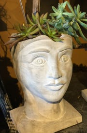 Head planters, including this one made out of cement, are a fun way to display plants these days.