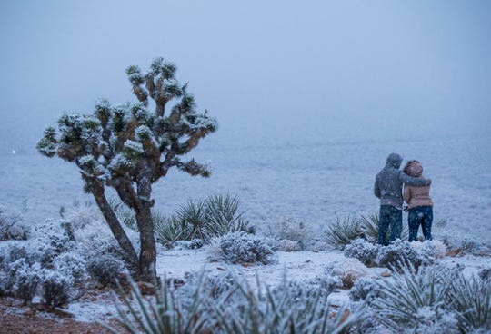 James Minner, of Las Vegas, left, and Candace Reid, of Albuquerque, N.M., watch as snow falls around the overlook at the Red Rock Canyon National Conservation Area outside of Las Vegas on Wednesday, Feb. 20, 2019. (Chase Stevens/ via AP)