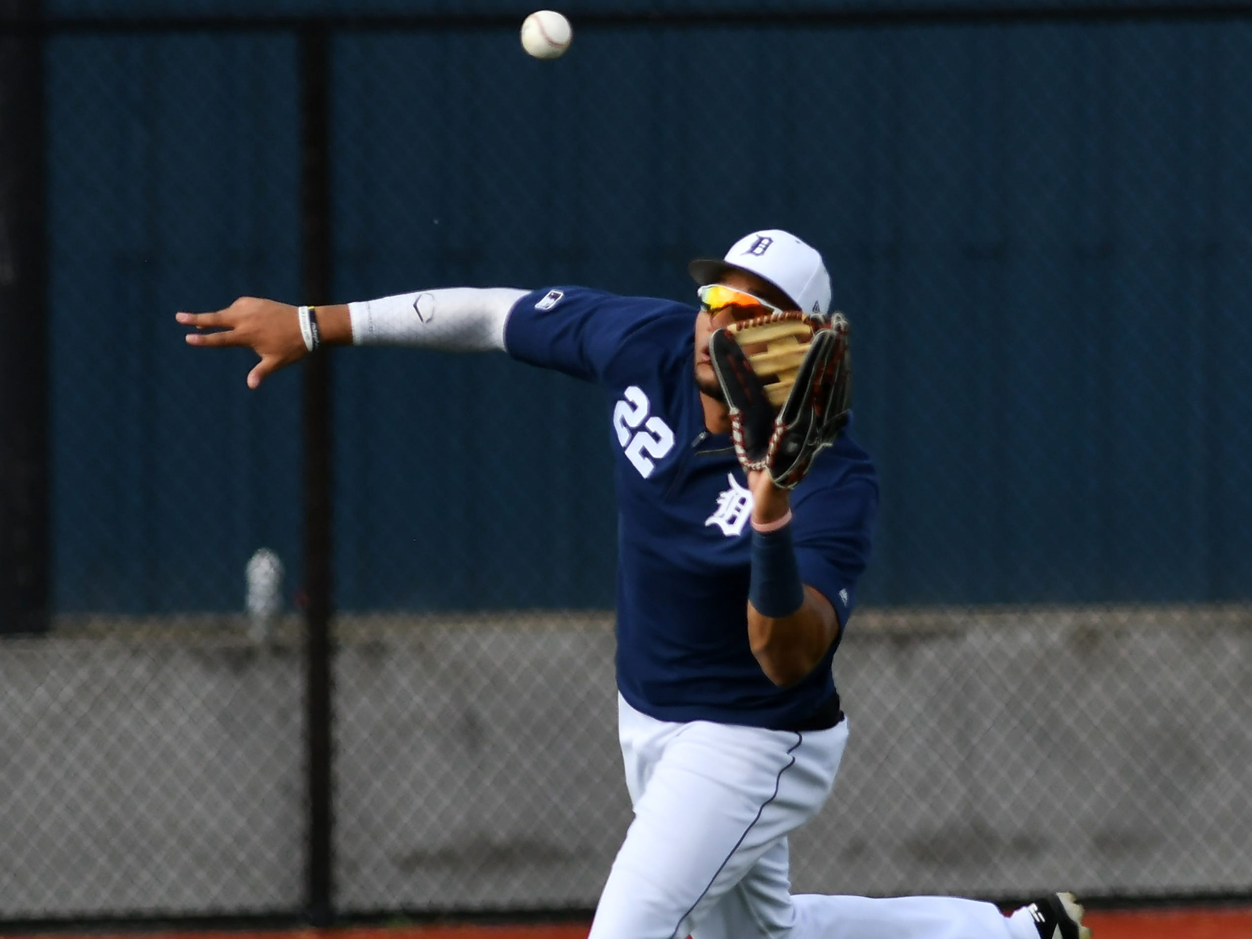 Tigers outfielder Victor Reyes makes a running catch on a fly ball during drills.