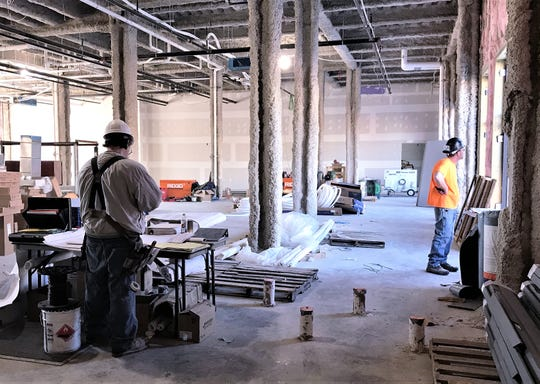 Workers make progress on first floor commercial space in a new mixed-used building on West Water Street in Elmira.