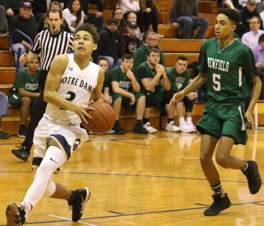 Kyreese Fisher of Elmira Notre Dame scores on a layup as Newfield's Daejahd Leckey follows behind during a Section 4 Class C first-round game Feb. 20, 2019 in Southport.