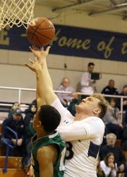 Ben Cook of Elmira Notre Dame puts up a shot over Newfield's Jalen Hardison during a Section 4 Class C first-round game Feb. 20, 2019 in Southport.