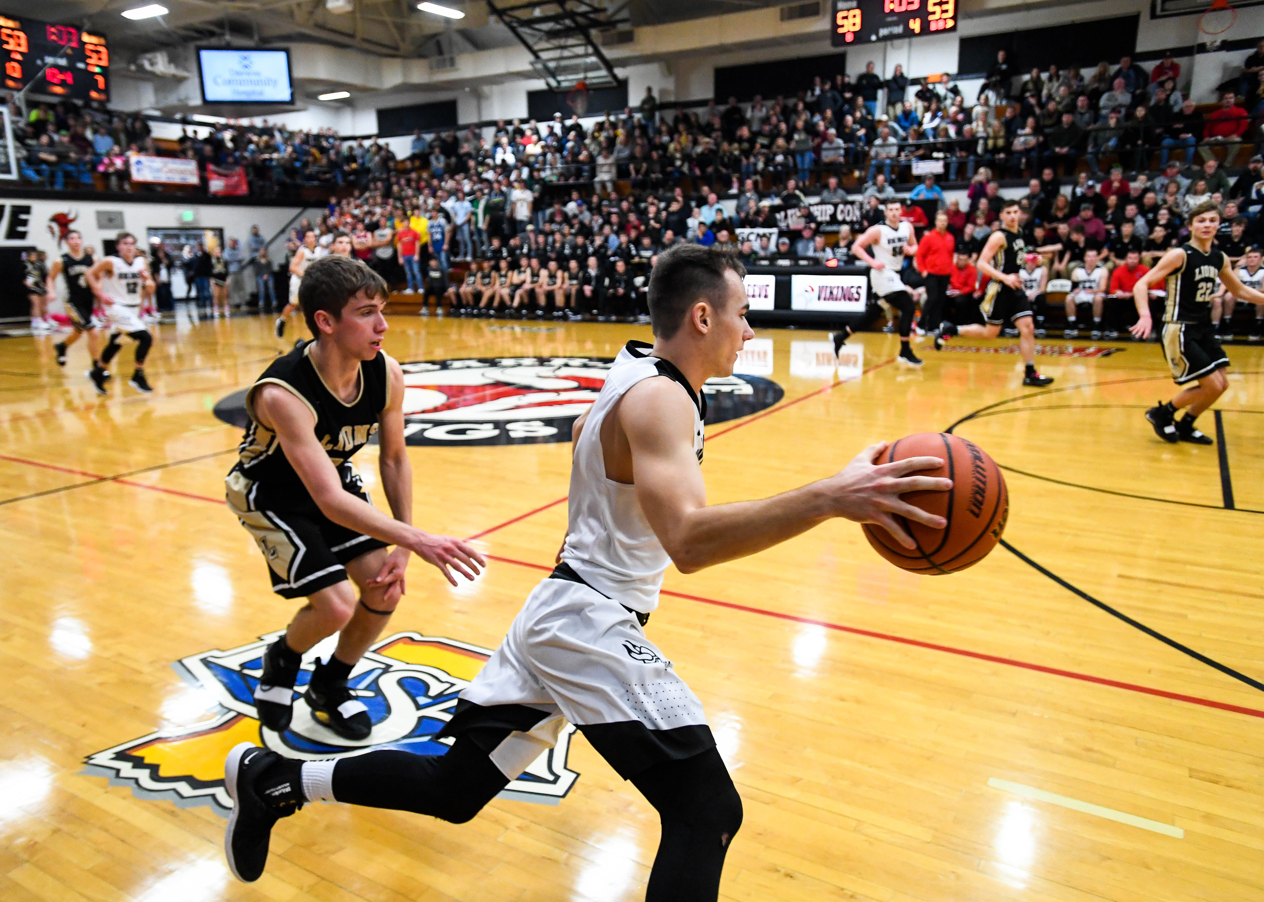 Barr-Reeve's Gabe Gladish (10) drives around Loogootee's Cade Chezem (24) during a rivalry match-up before a packed house in Barr-Reeve's 2,100 seat Kavanaugh Kourt Friday, January 11, 2019.