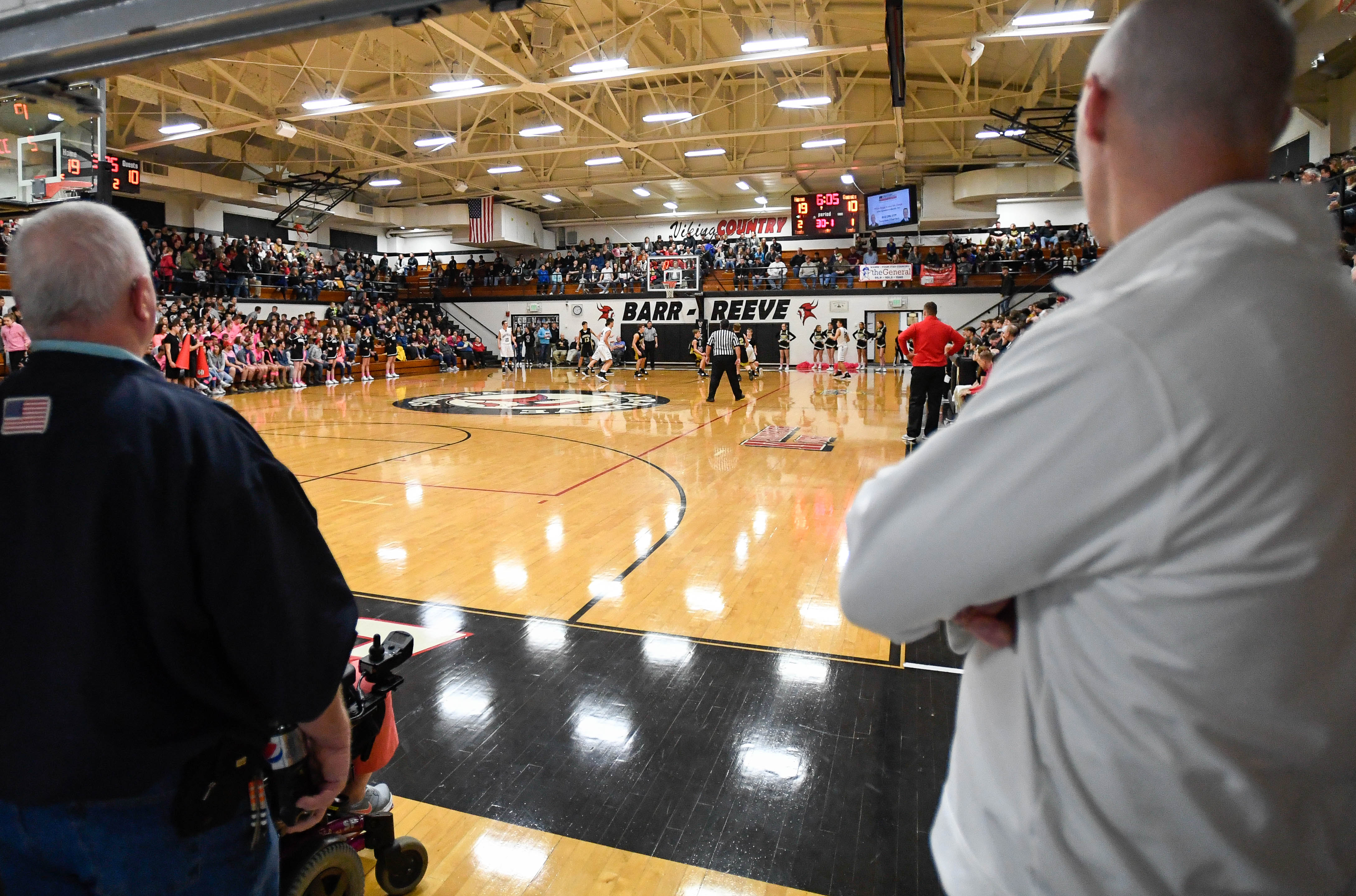 Paul Arvin, left, and Jeff Doyle frame the doorway as they watch the junior varsity game at the rapidly filling Kavanaugh Kourt at Barr-Reeve  high school Friday, January 11, 2019.