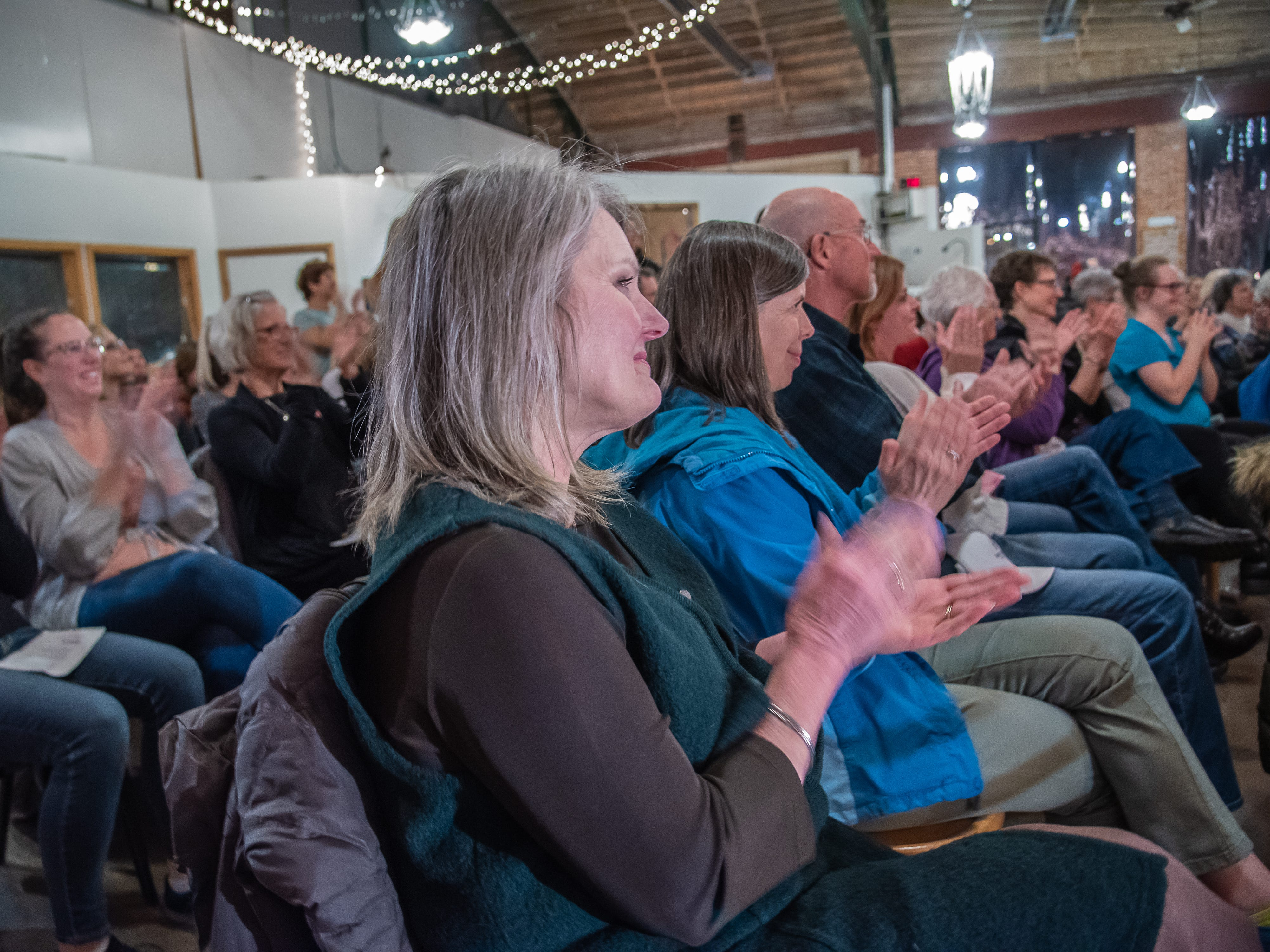 Audience member Tonya Schwolert applauds storyteller Margaret Carr at the conclusion of the Coloradoan Storytellers Project at Everyday Joe's Coffee House on Wednesday, February 20, 2019, in Fort Collins, Colo.