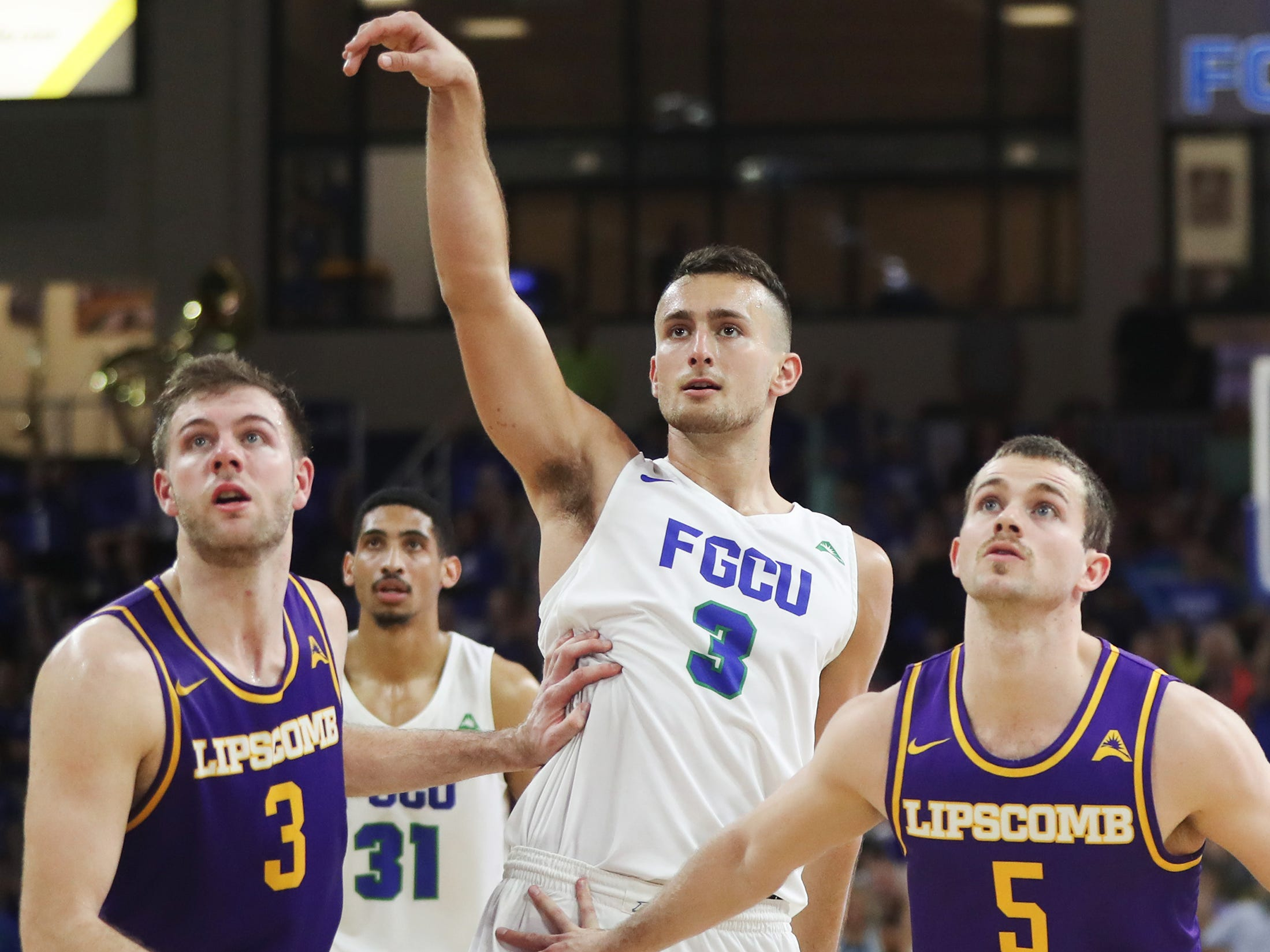 Florida Gulf Coast University's Christian Caryle, center, makes a late-game free throw against Lipscomb's on Wednesday at FGCU in Fort Myers. FGCU beat Lipscomb 67-61.