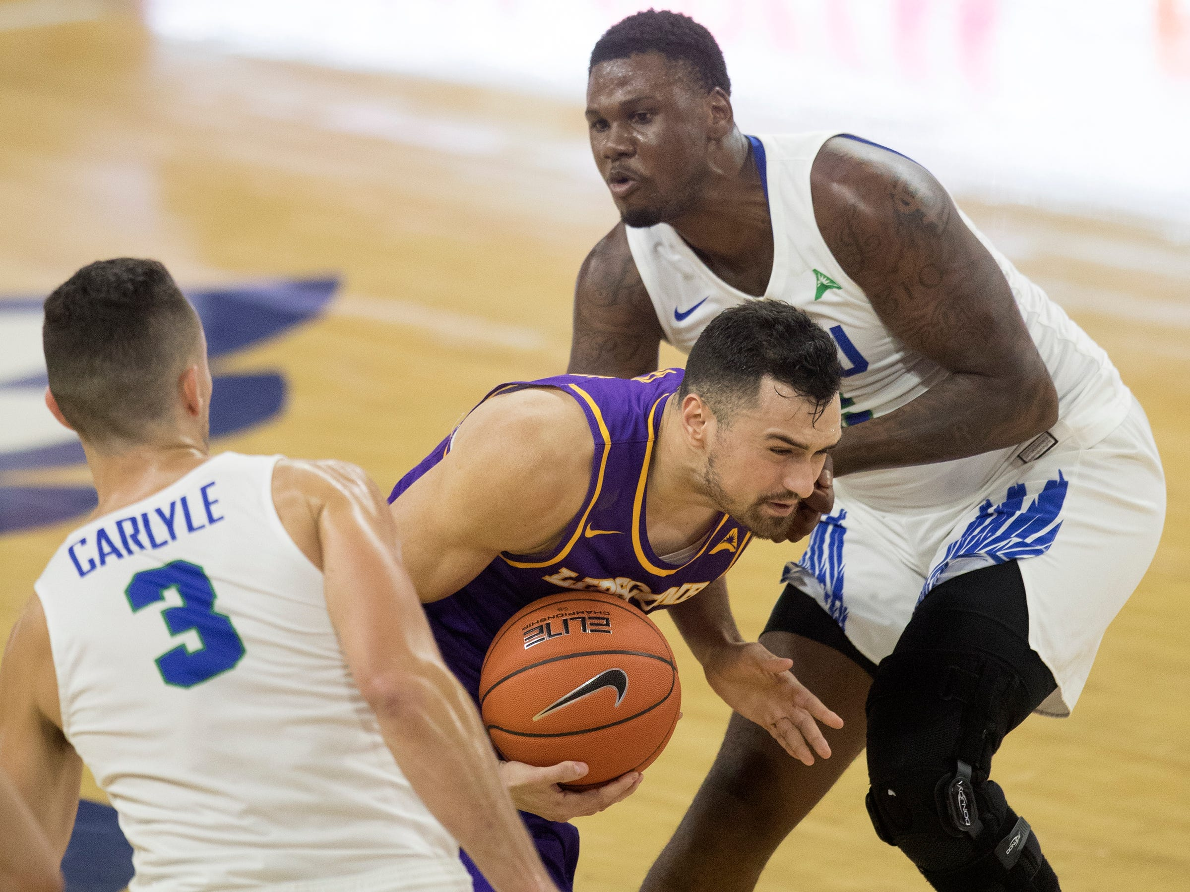 Lipscomb's Andrew Fleming, center, drives to the basket against FGCU on Wednesday at FGCU in Fort Myers. FGCU beat Lipscomb 67-61.
