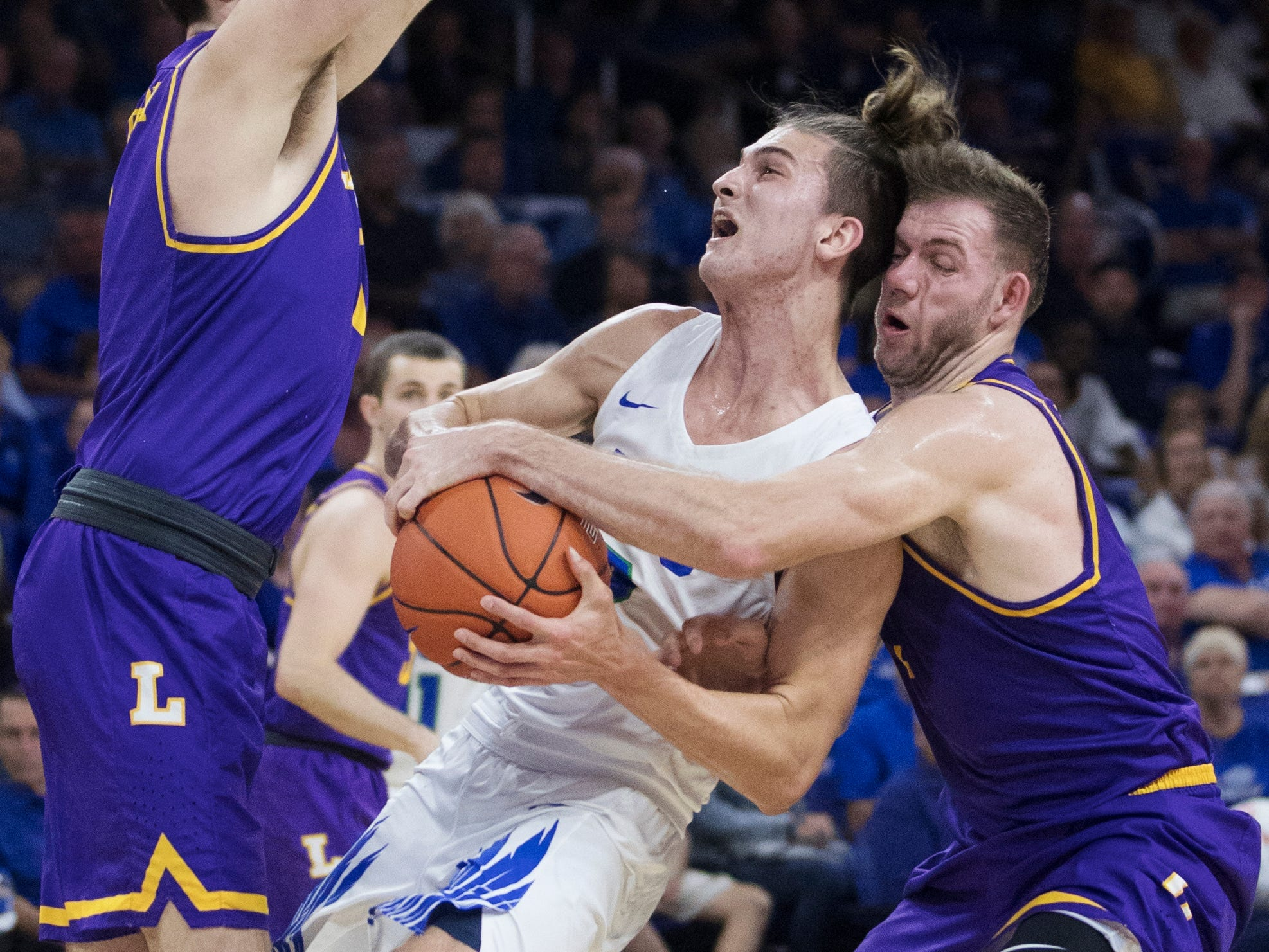Florida Gulf Coast University's Caleb Catto drives to the basket against Lipscomb's Rob Marberry, left, and Michael Buckland on Wednesday at FGCU in Fort Myers. FGCU beat Lipscomb 67-61.