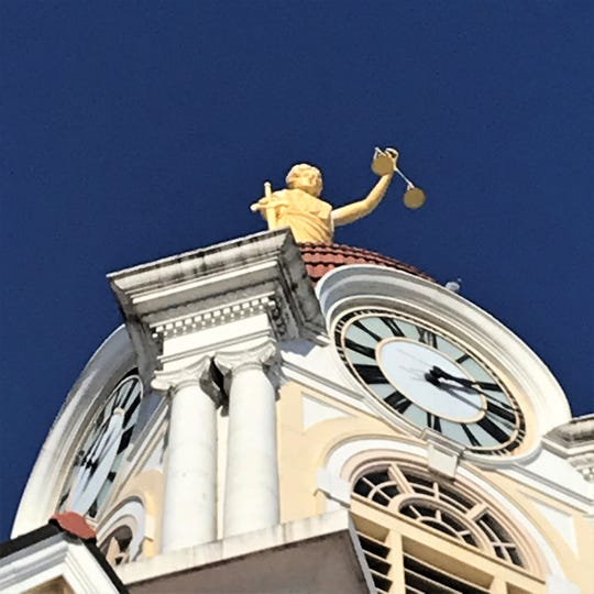 A statue of Themis is seen at the top of the Oconto County Courthouse in Oconto, Wisconsin.