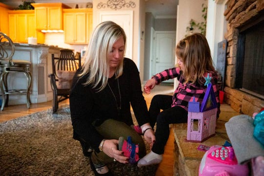 Kerri Gray puts shoes on her daughter, Bailey, 2, before heading to the backyard. In 2013, Gray's son, Jackson, died from suffocation by bedding at 12 weeks old while staying in a home day care.