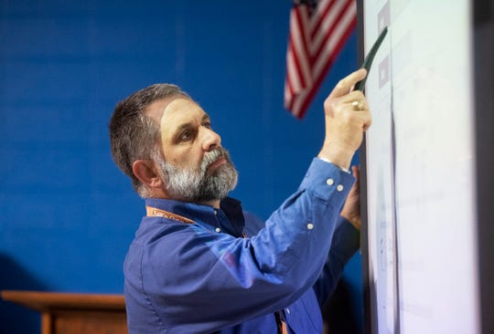 Light from a Promethean board spills onto David James while he teaches at Northwest Middle School in Travelers Rest Thursday, Feb. 21, 2019. James has taught at the school for 21 years.