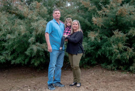 Frank and Kerri Gray hold their daughter, Bailey, 2, in their arms while in the backyard. In 2013, their son, Jackson, died from suffocation by bedding at 12 weeks old while staying in a home day care. In the wake of another infant's death, a state law was passed allowing regulators, for the first time ever, to conduct unannounced inspections of these homes without needing a complaint.