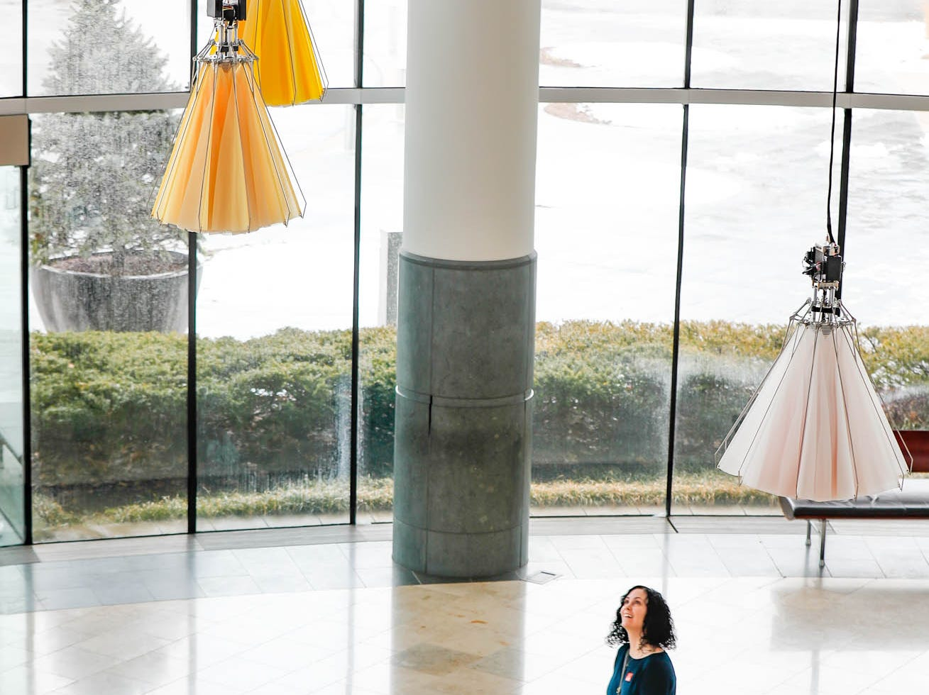 "Denise Orendi and her daughter Athena Orendi walk under the ""Meadow"" kinetic sculptural art installation by artist collective Studio Drift inside the Indianapolis Museum of Art at Newfields on Wednesday Feb. 20, 2019. The installation marries art and science, using computer programs and sensors to open and close the flowers. The installation runs Feb. 22, 2019-Feb. 23-2020."