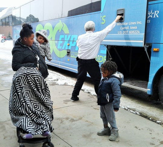 Victoria Gibbs of Cedar Rapids organizes her three small children – one sheltered under the blanket placed over the stroller -- after riding the 380 Express to its stop near the University of Iowa Stead Family Children's Hospital.  Driver Scott Bemer closes a luggage bay in the background.