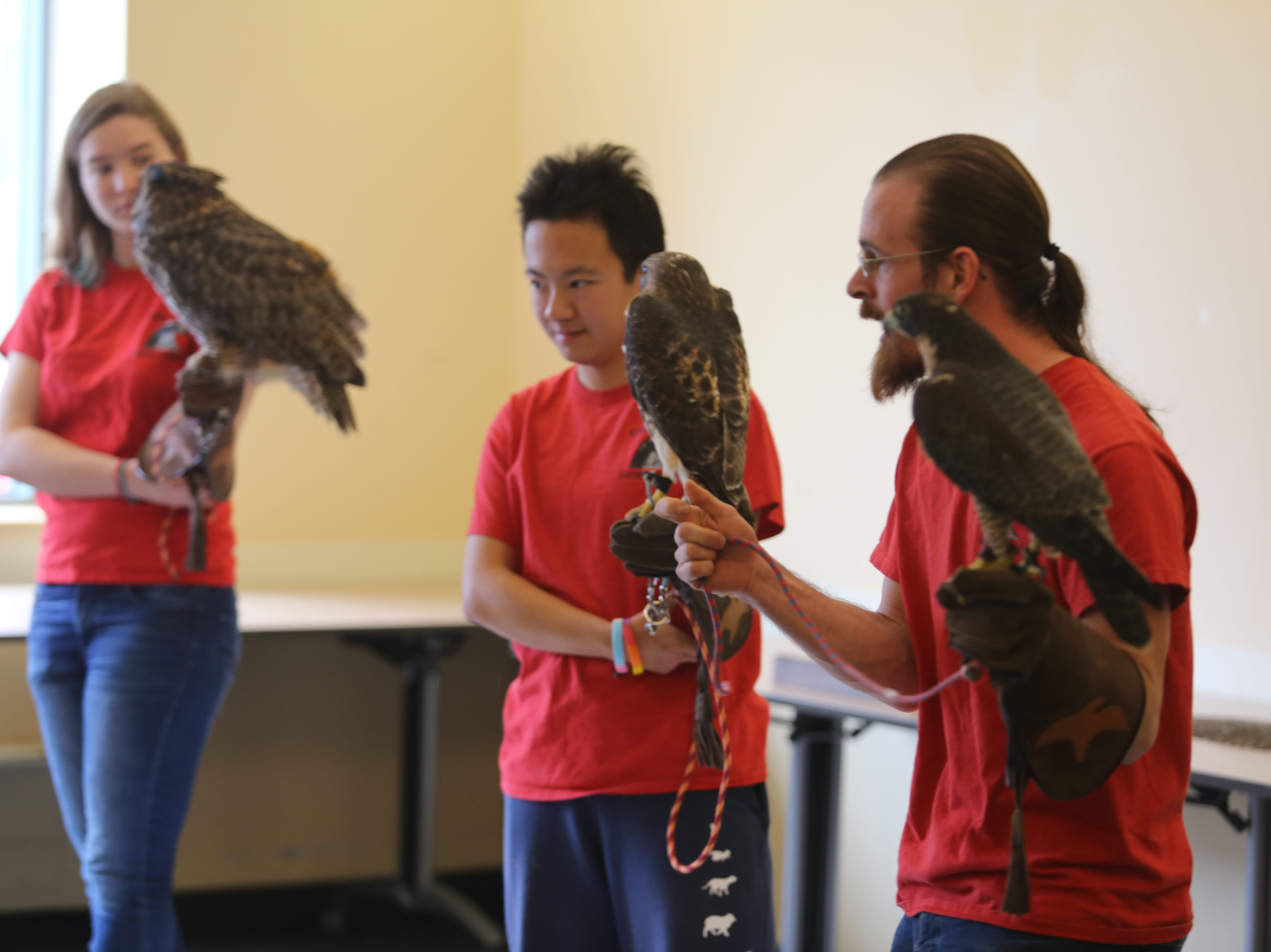 Left to right: Claire Jones, Pit Wang and Andrew Schmalfuss are students in the Cornell Raptor Program. Jones is holding an owl named Gertrude meanwhile Wang and Schmalfuss are holding two other raptors.