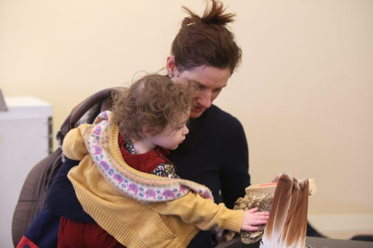 Margaret Soulstein, of Ithaca, and her two-year-old daughter Sylvia Soulstein examine raptor feathers.