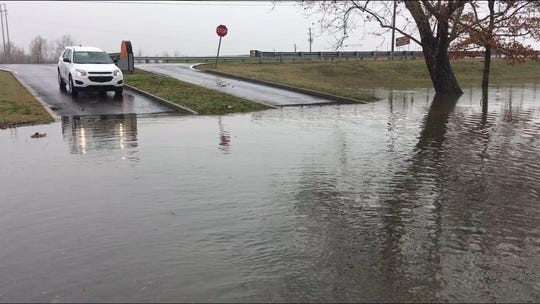A vehicle sits above standing flood water on the roadway near an entrance to Reelfoot State Park.
