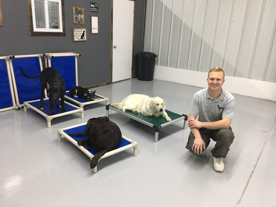 "Jason DeCort is certified by Starmark Academy as an Animal Behaviorist and Dog Training Specialist. The small black and white dog, Sukie, is one of his original foster dogs who ""helped"" him choose his career."