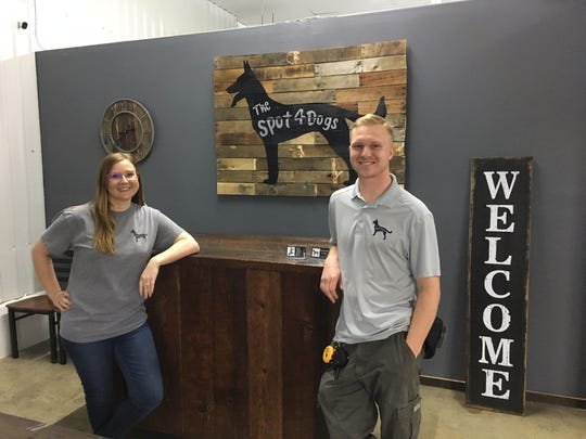Katelyn and Jason DeCort run The Spot 4 Dogs on Grand Avenue. Katelyn designed and made the sign over the desk from an old pallet. Feb. 20, 2019.