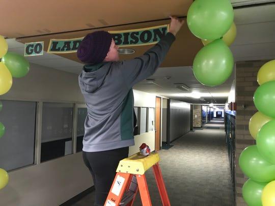 Niki Tucker decorates a hallway inside Benton Central.