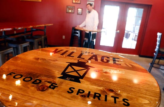 Jeff Dupler moves stools inside The Village Food and Spirit Thursday morning, Feb. 21, 2019, in Amanda. Dupler opened the new restaurant with his wife Jody.