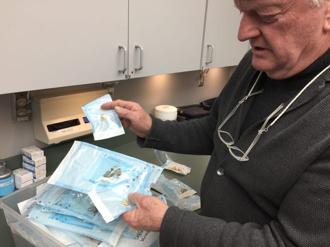 Dr. Fredric Bonine sifts through a box of extracted teeth, fillings and old dental appliances at his Genoa Township dental office, Thursday, Feb. 21, 2019.