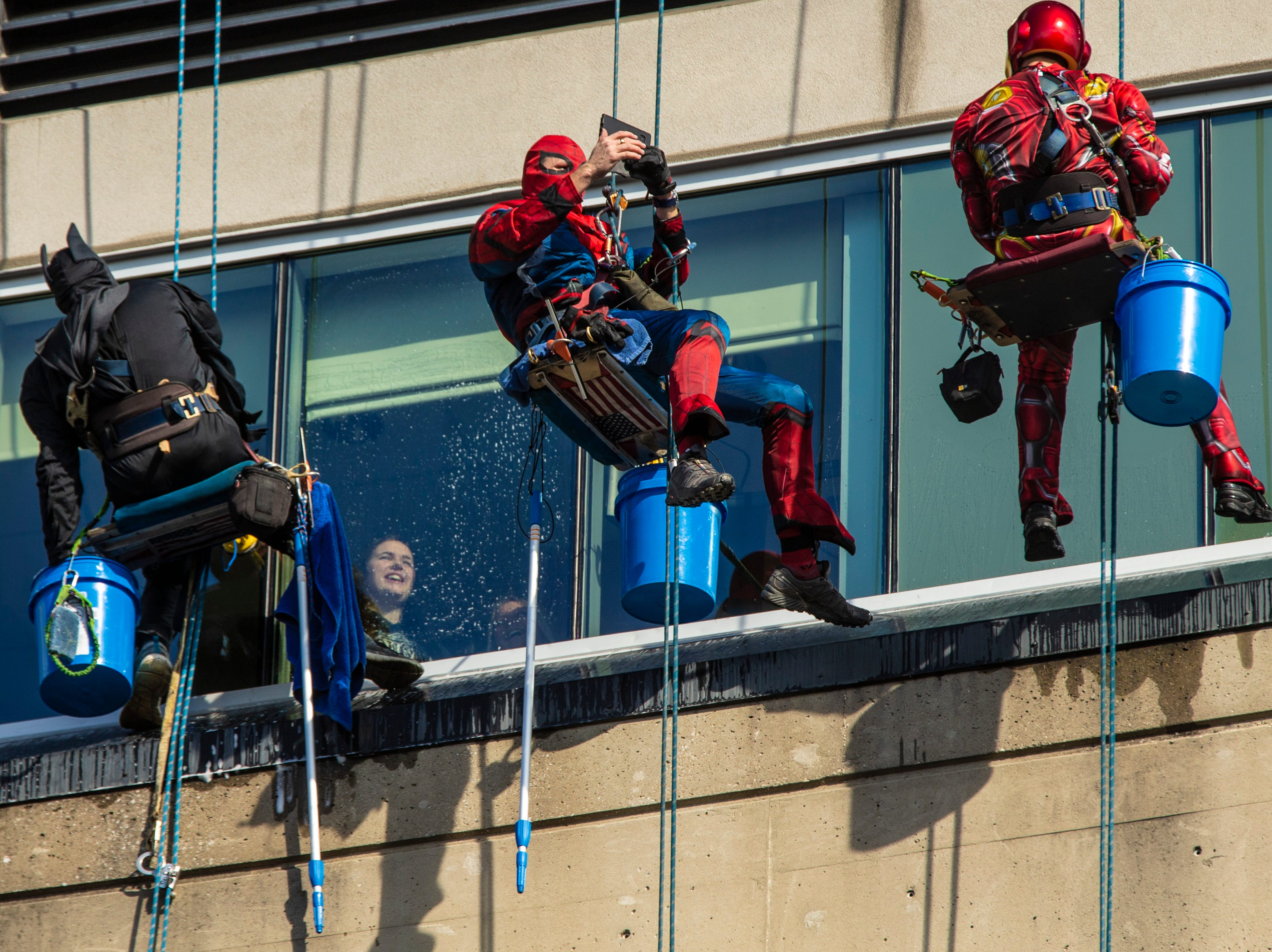 William Hart, from left, Duke Hart and Joe Haist with Pro Clean International wear super hero costumes while cleaning the windows at Norton Children's Hospital on Thursday. Feb. 21, 2019