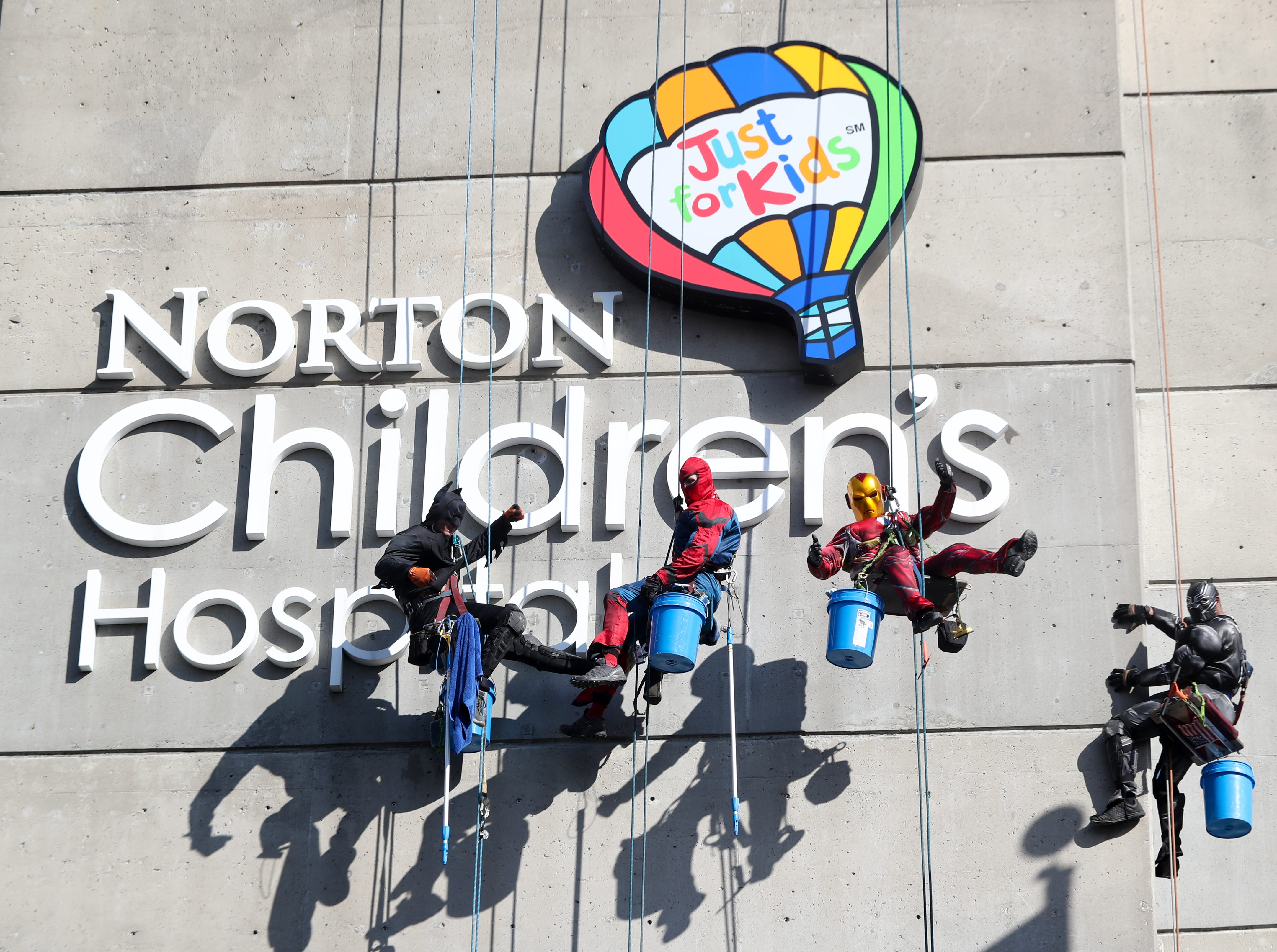Pro Clean International cleans the windows at Norton Children's Hospital on Thursday morning dressed as Superheroes.  William Hart is dressed as Batman. Lonnie Hart is dressed up as Spider-Man. Joe Haist is dressed as Ironman and Lionel Bass is dressed as the Black Panther.  Feb. 21, 2019