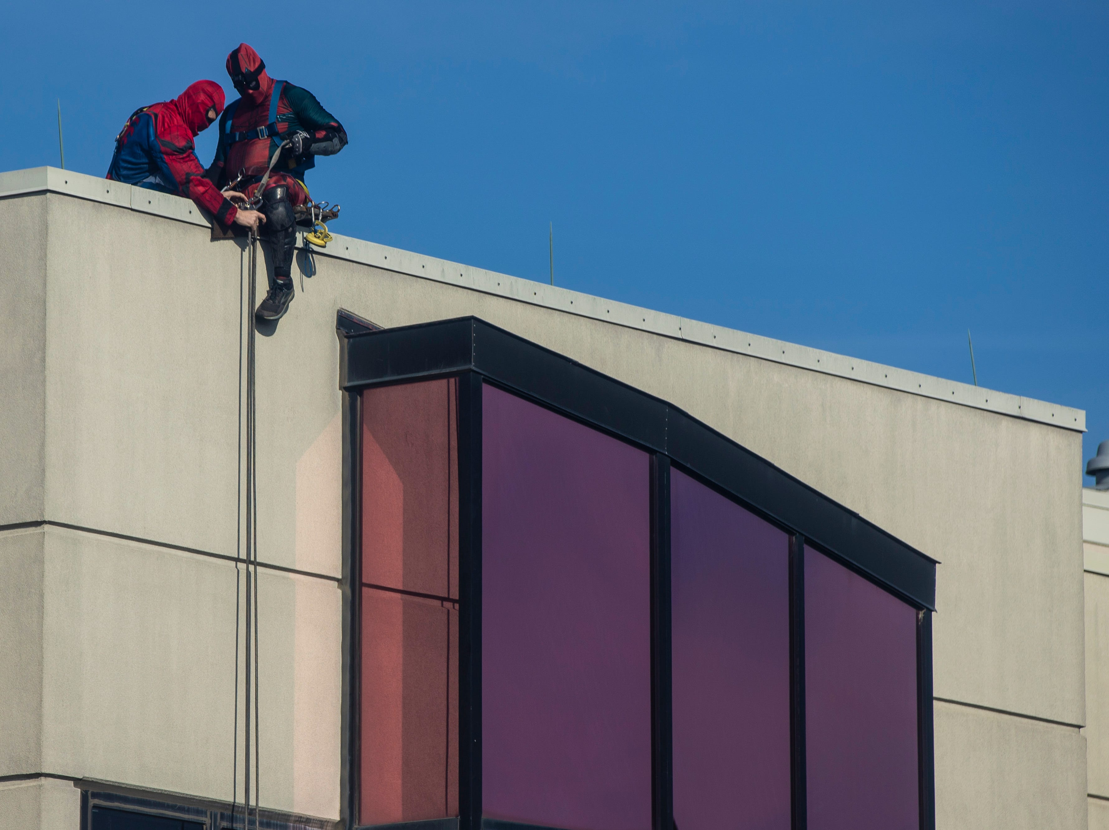 Duke Hart, left, and Johnny Haist with Pro Clean International prepare to descend as the team wore super hero costumes while cleaning the windows at Norton Children's Hospital on Thursday. Feb. 21, 2019