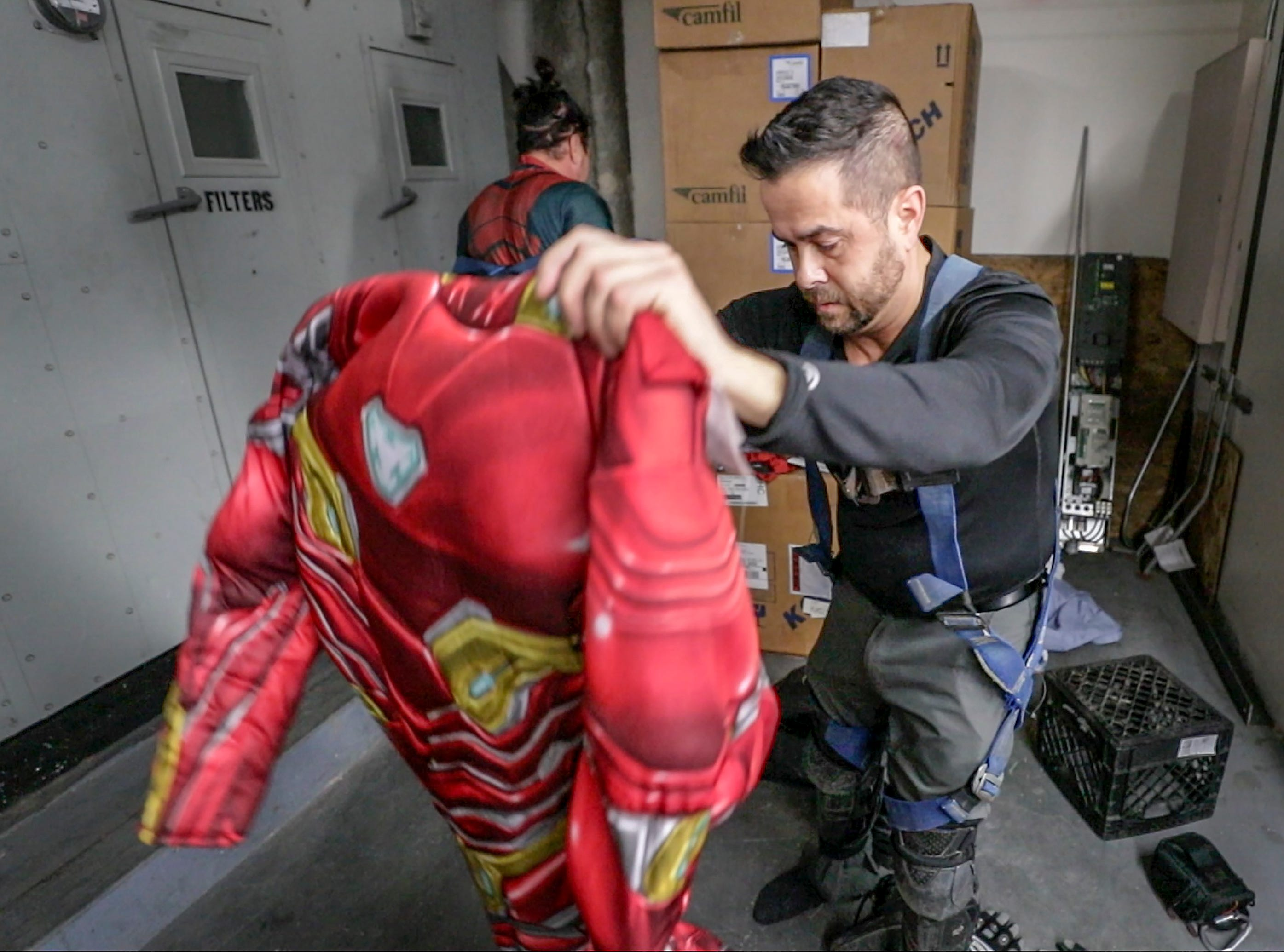 Window washer Joe Haist, with Pro Clean International, portraying Iron Man, puts on his costume before going over the roof of Norton Children's Hospital on Thursday morning.February 21, 2019