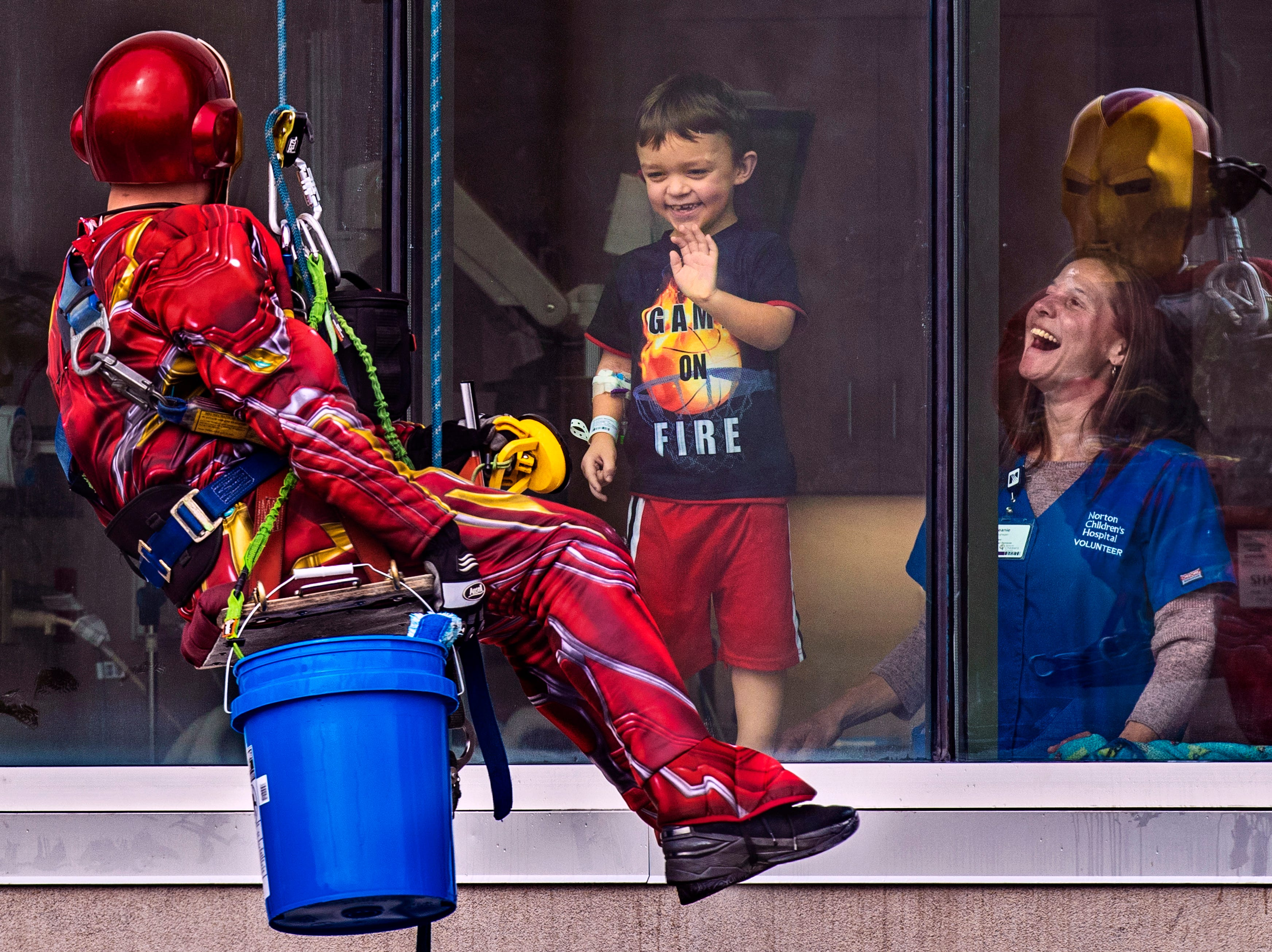Joe Haist, from left, shares a moment dressed as Iron Man with Brennen Wilkerson, 6, as the young boy and volunteer nurse Beanie Geoghegan look on as Pro Clean International cleaned windows at Norton Children's Hospital on Thursday dressed as super heroes. Feb. 21, 2019